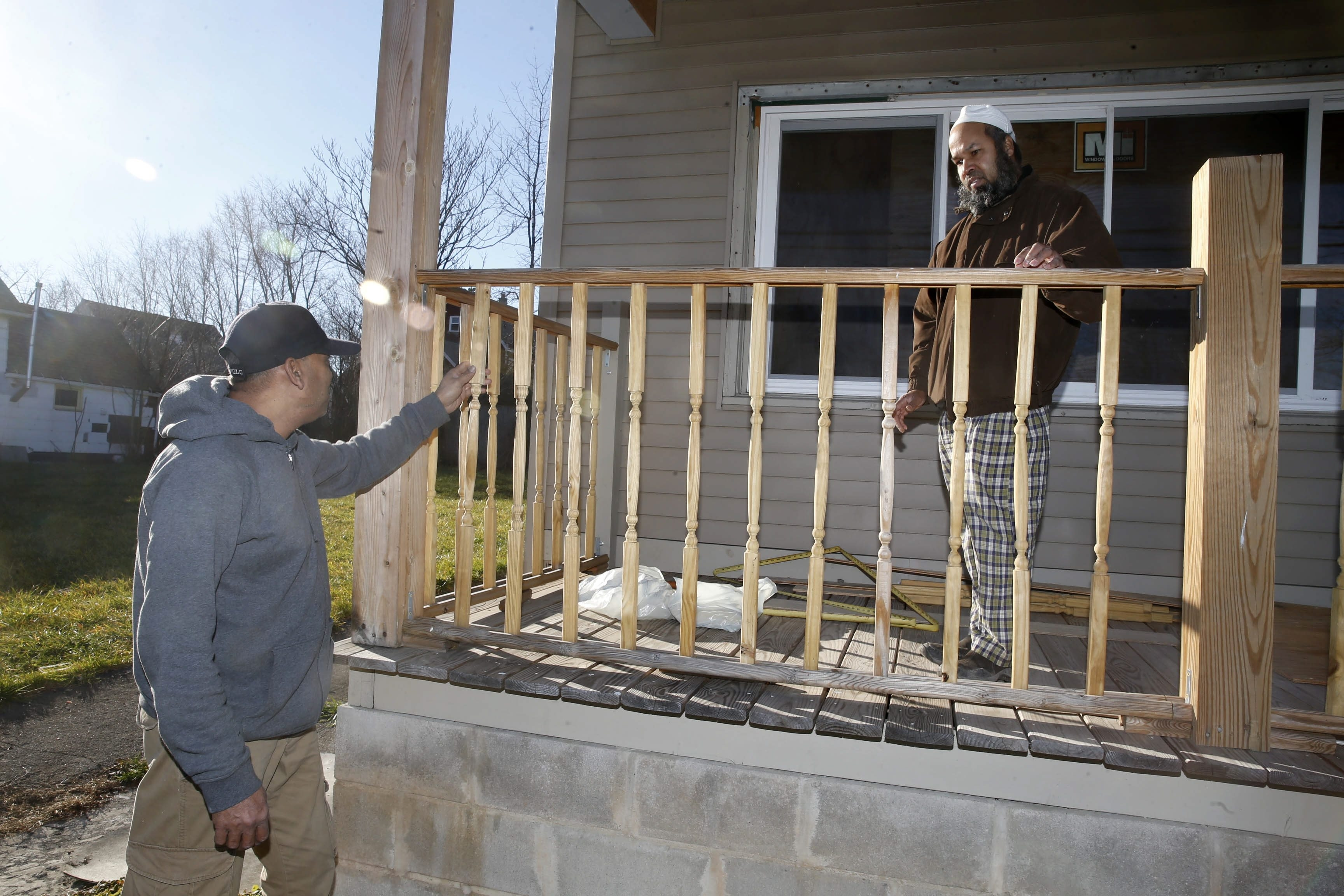 Bangladeshi native Sheikh Rahman, right, and his cousin, Juberi Hasan, work on the porch of a family member's house on Rother Street. Rahman says he moved to Buffalo from Queens in 2006 because of Buffalo's better real estate prices and quality of life. (Robert Kirkham/Buffalo News)