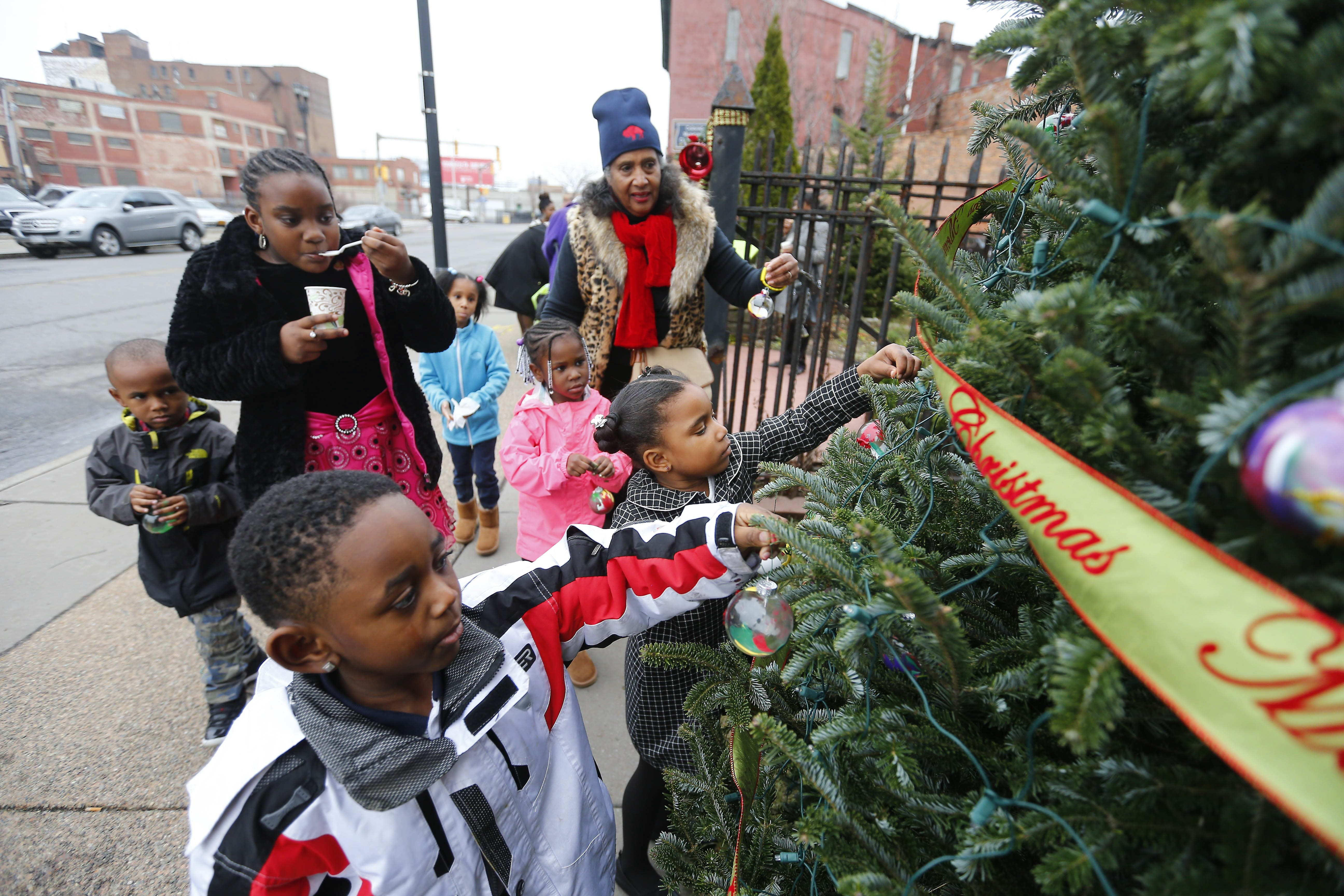 Eunice Lewin, top center, urges kids to hang their handmade  ornaments on a tree during a Christmas  celebration in front of Michigan Street Baptist Church. See a photo gallery at buffalonews.com.