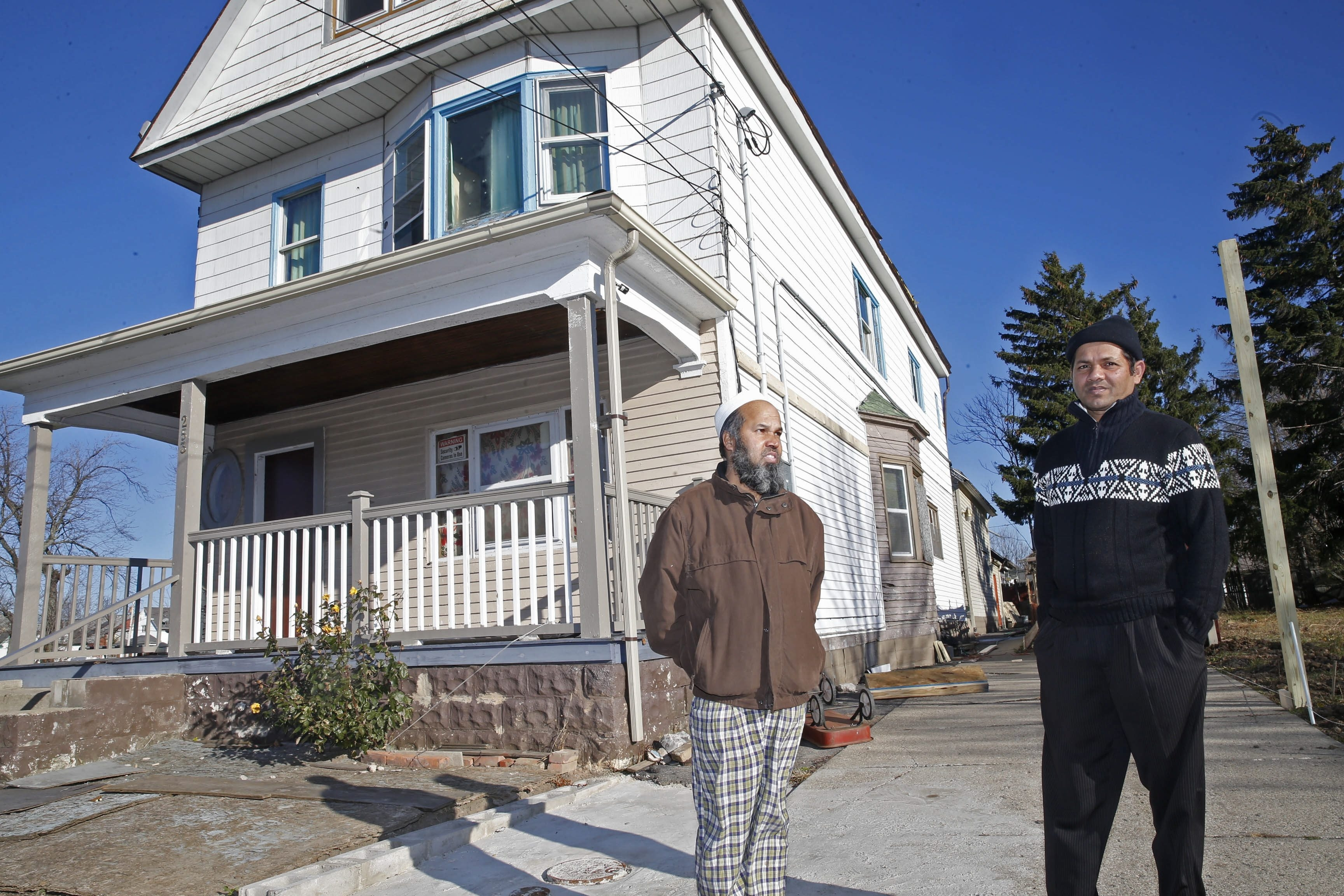 Bangladesh native Sheikh Rahman, left, and neighbor Kazi Ali Ahasan discuss the improvements they are making on their homes on Rother Avenue. Rahman moved in 2006 from Queens to Buffalo, where a dollar goes much farther.