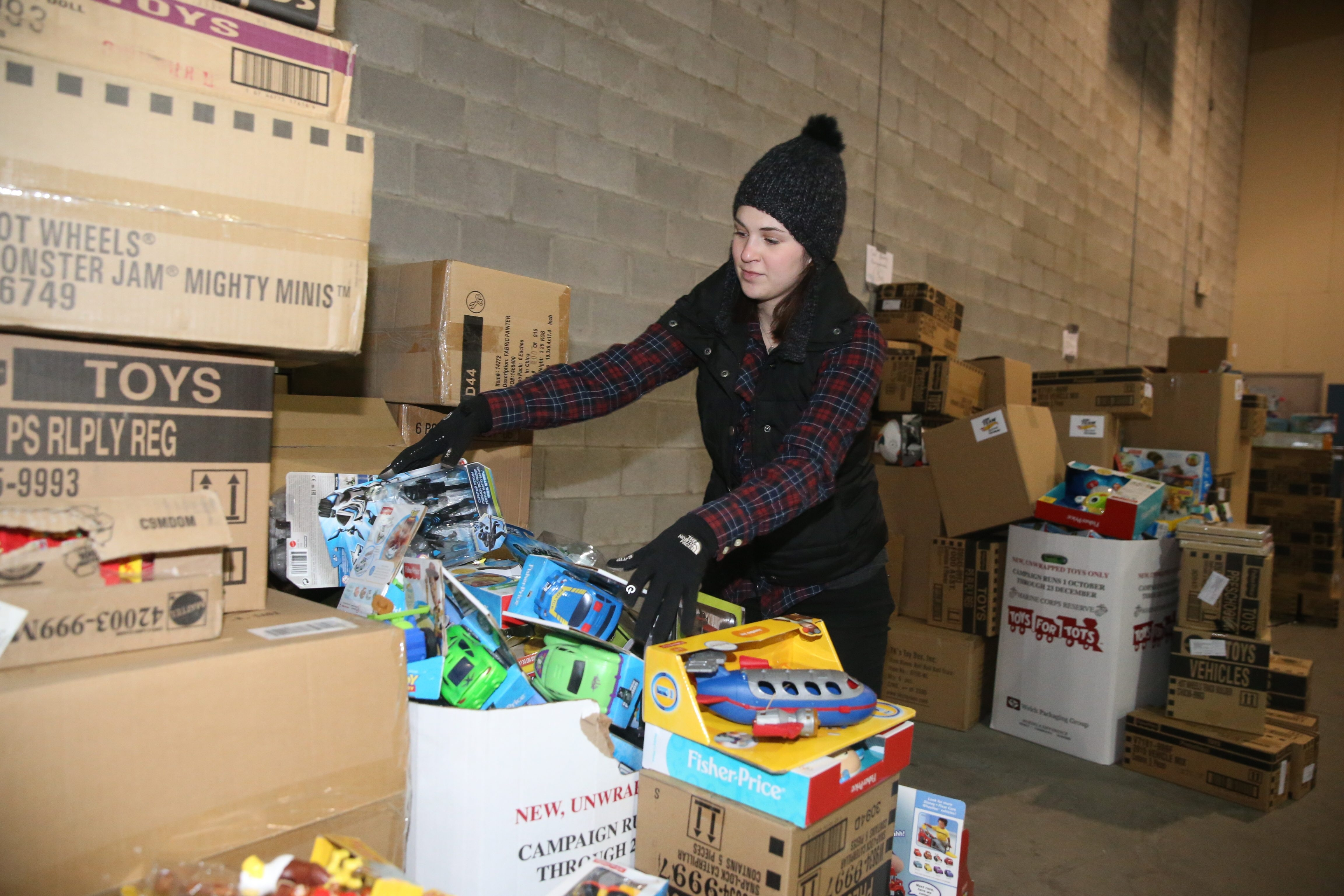 Fisher-Price designer Becca Freund, of Orchard Park, a volun- teer for News Neediest, sorts out donated toys in Tonawanda.