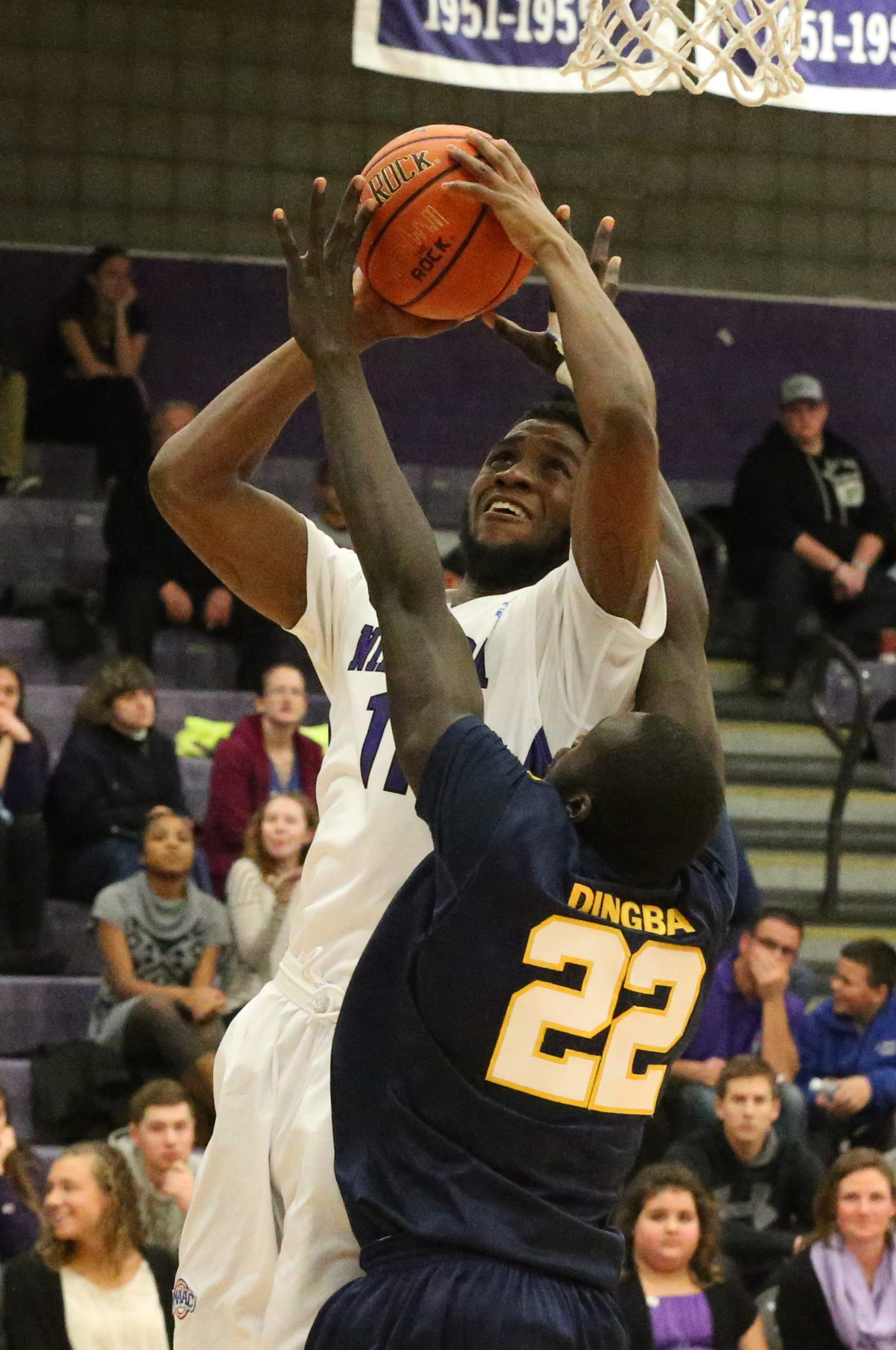 Niagara's Marvin Prochet scores a basket over Quinnipiac's Samuel Dingba in the first half of Friday night's victory at the Gallagher Center.