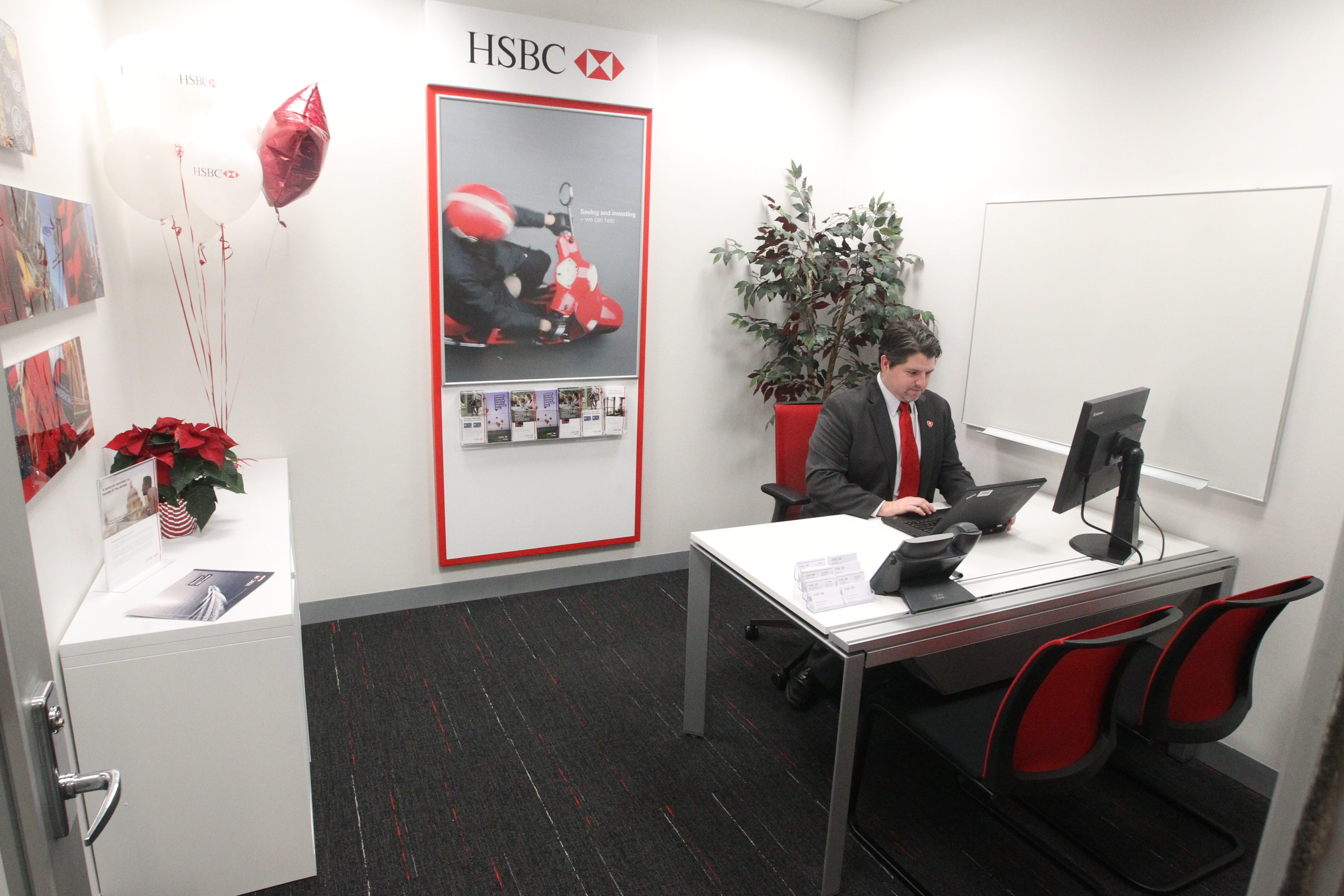 Alex Woods, a premier relationship manager for HSBC Bank USA, works at the refurbished space where a new employee financial ser- vices center was unveiled in offices at Walden Avenue and Dick Road. It makes it easier for staff members and families to be customers.