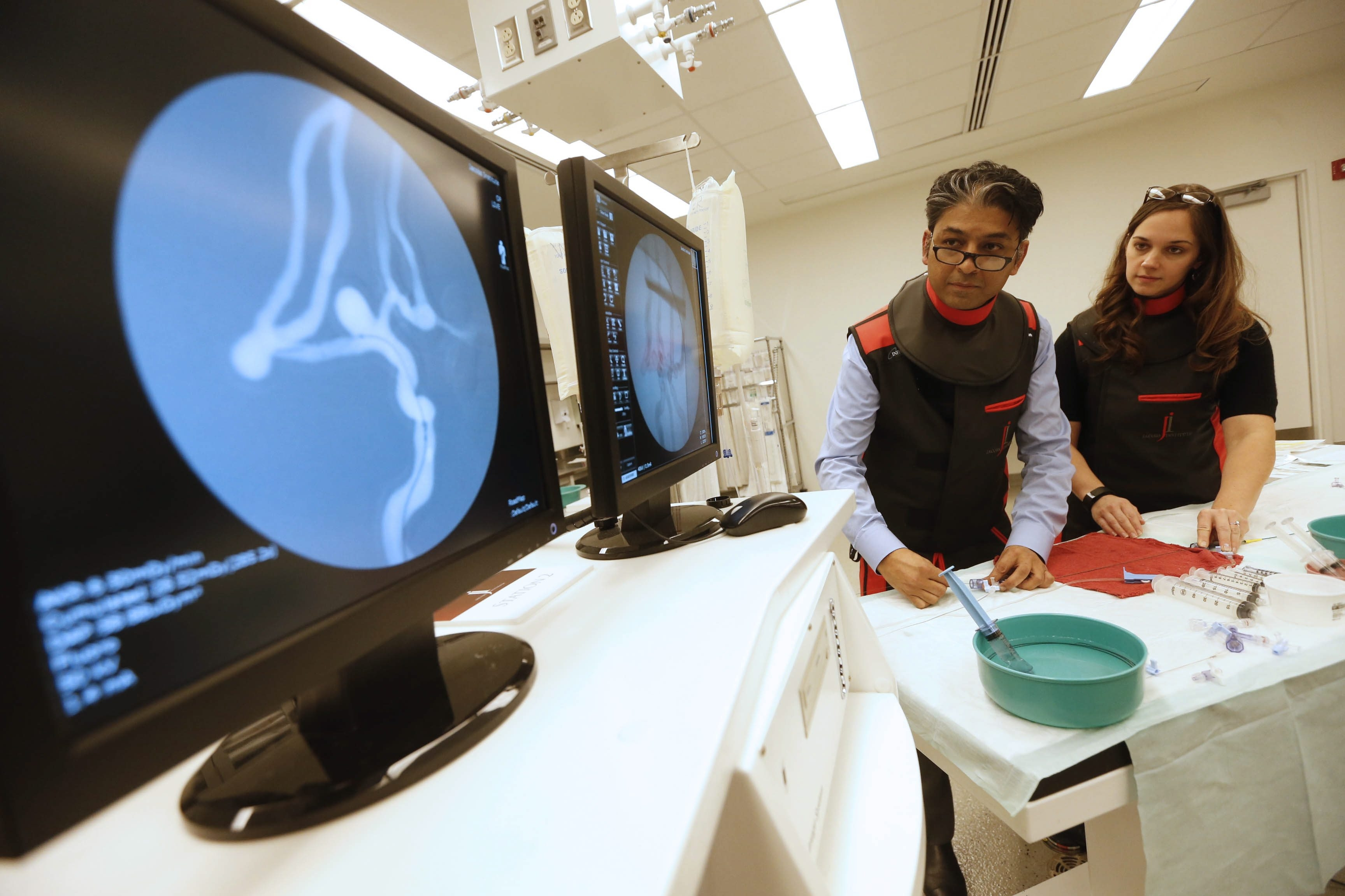 """Dr. Adnan Siddiqui, chief medical officer at the Jacobs Institute, left, and research associate Liza Pope simulate a procedure with a 3-D model. """"This is going to become the standard of care,"""" Siddiqui said."""