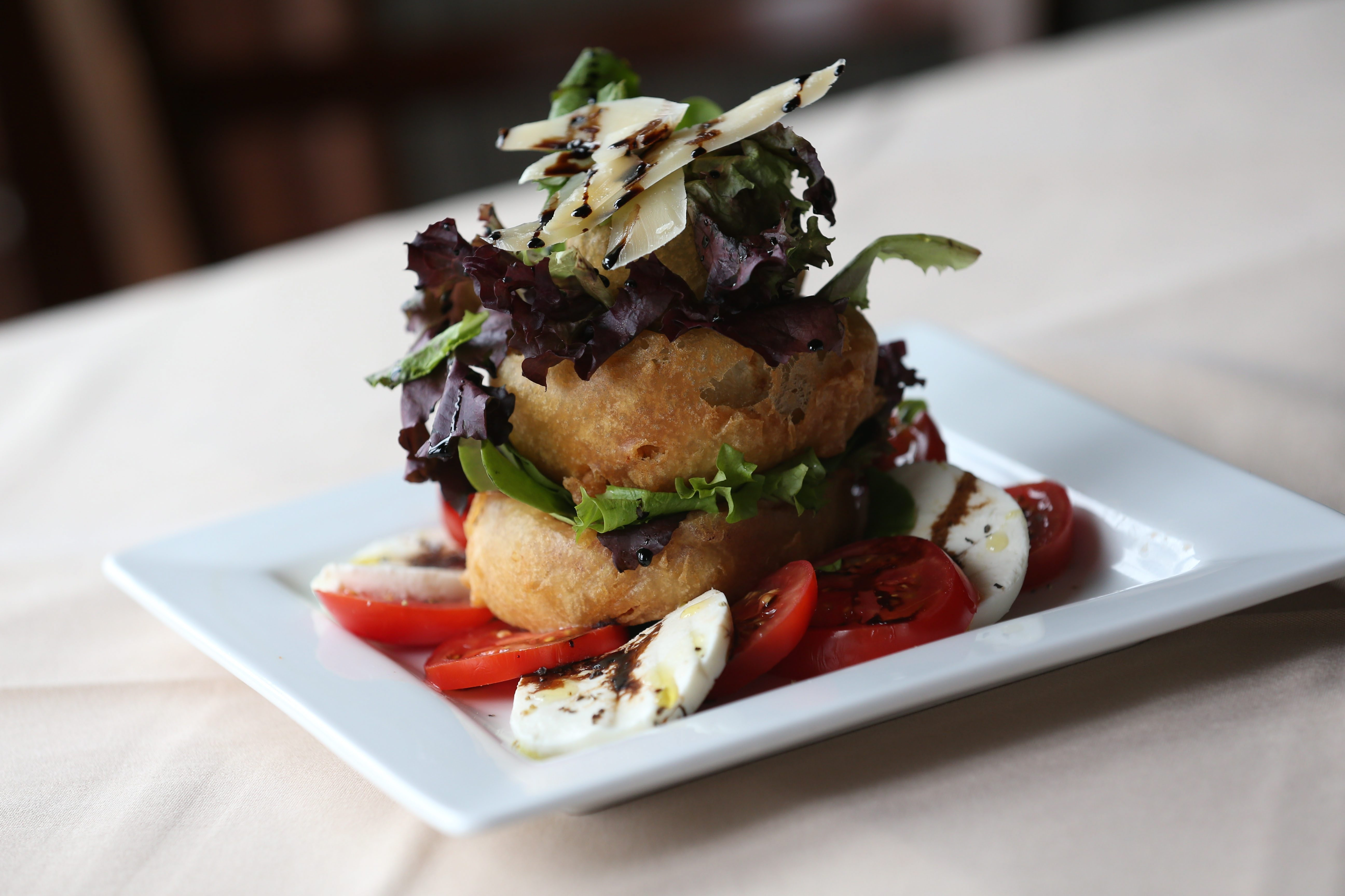The Pepper and Onion Stack at Rick's on Main includes bell pepper, poblano pepper and sweet onion tempura fired and stack atop each other, then stuffed with lightly dressed greens and served over slice tomatoes and fresh mozzarella.