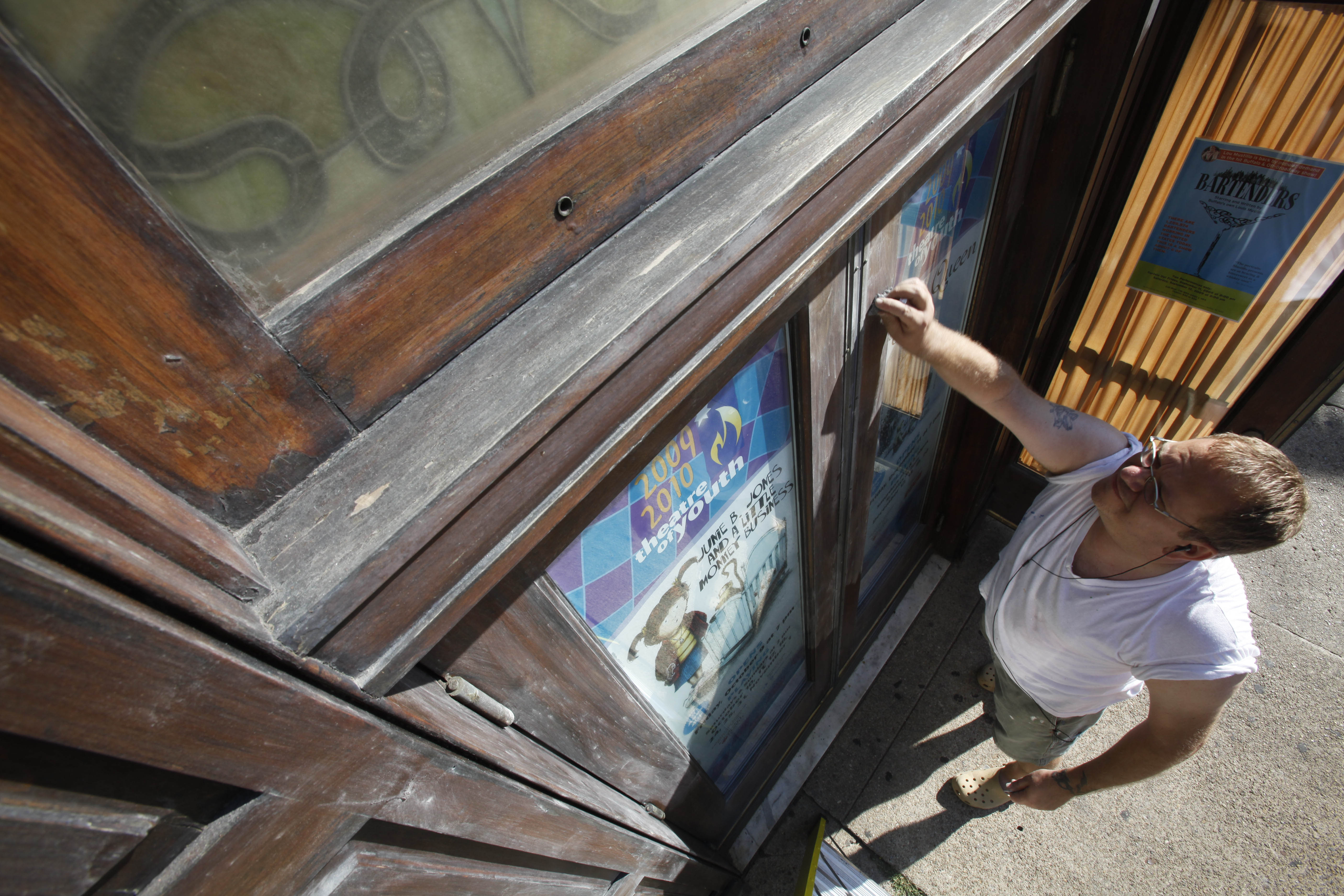Ken Shaw, head of design at the Theatre of Youth on Allen Street, refinishes the woodwork on the theater's front door Sept. 3, 2009, as he prepares for the upcoming Curtain Up! event. (Photo by Derek Gee/Buffalo News)