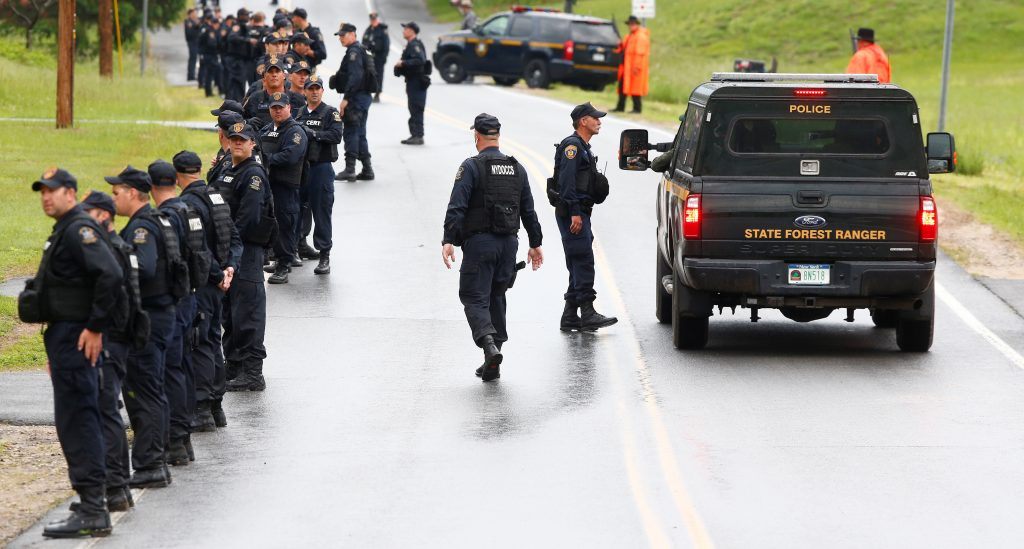 Law enforcement officers search a neighborhood in Cadyville, N.Y., near Dannemora, where two violent inmates escaped from prison nearly a week ago, June 12, 2015. Joyce Mitchell, a prison worker who had befriended the killers before their escape, was arrested for providing material assistance, authorities said Friday. (Nancie Battaglia/The New York Times)