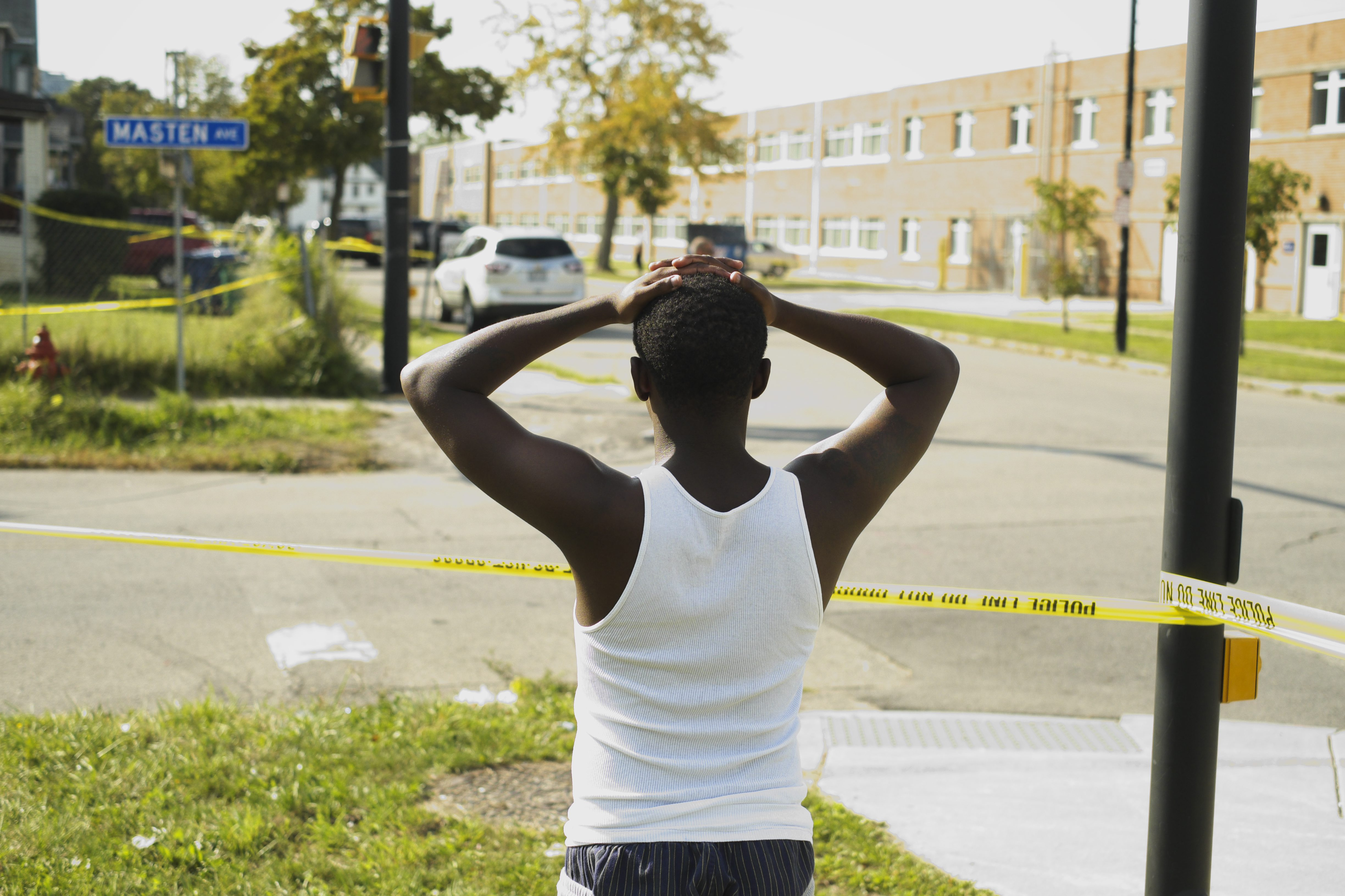 A young man watches from the edge of the crime scene as Buffalo police investigate a homicide outside Buffalo Academy of Visual and Performing Arts, Friday, Sept. 24, 2015.  The victim, Reginald L. Barnes, 28, was shot inside a vehicle at the intersection of Masten and Woodlawn avenues.  (Photo by Derek Gee / Buffalo News)