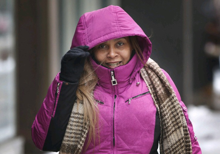 Rosa Mesa of Buffalo braces herself from the drizzle Tuesday while walking on Main Street. (Derek Gee/Buffalo News)
