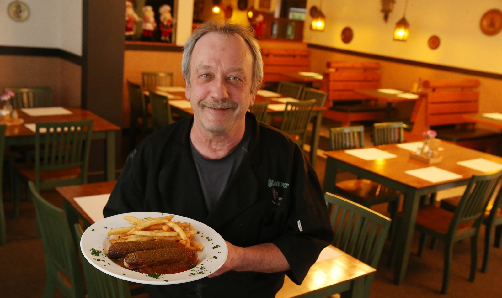 Black Forest Adler owner Gerhard Braun presents the restaurant's curry sausage in 2016. (Sharon Cantillon/News file photo)