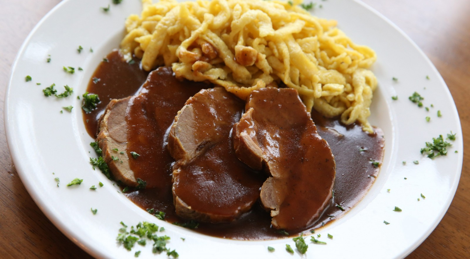 Pork comes in a dark beer gravy and is served with homemade spaetzle. (Sharon Cantillon/Buffalo News)