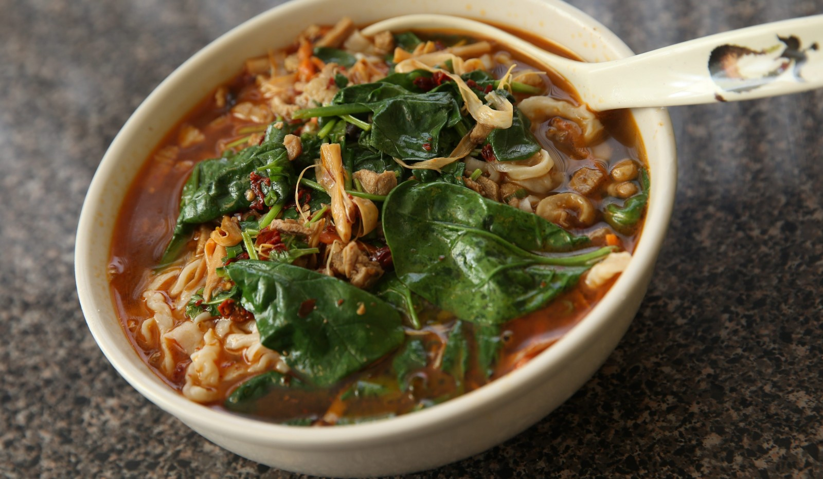 Noodles in a bit of spicy chile-laced broth, tangy with vinegar, and a jumble of vegetables. (Sharon Cantillon/Buffalo News)