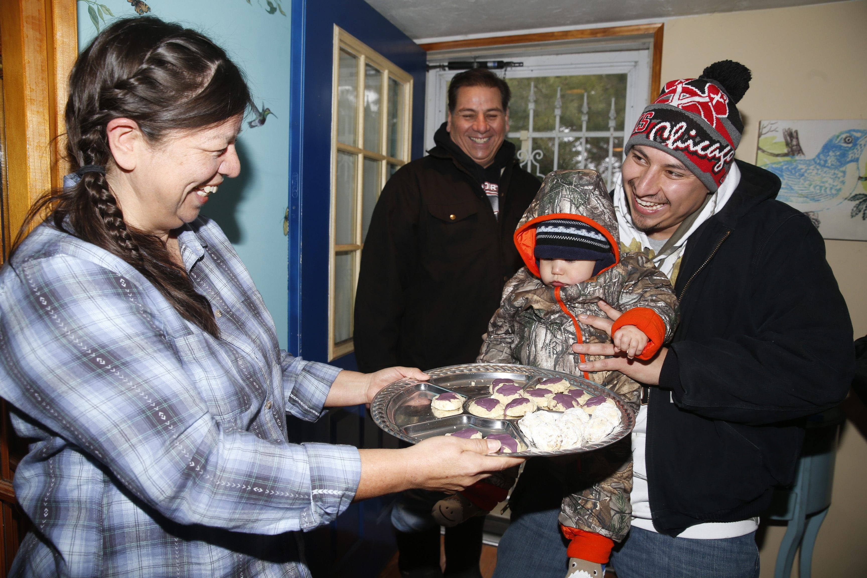 "Sam Crogan III, 9 months; his father, Sam Crogan Jr.; and his grandfather, Sam Crogan Sr., stop by Angela Jonathan's home on Mount Hope Road Friday to take part in ""Nu Ya,"" a Native American celebration involving baked goods."