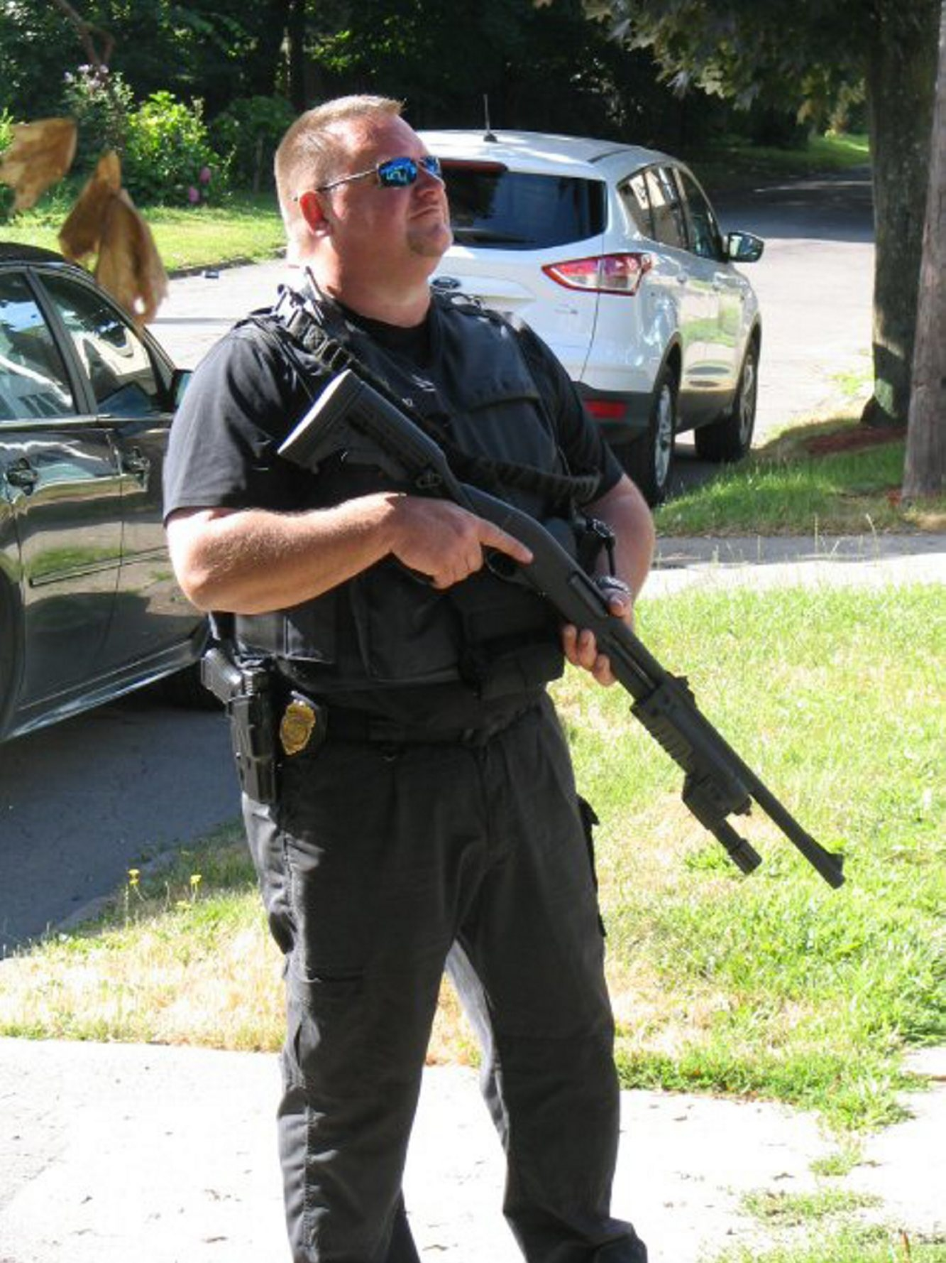 An Erie County probation officer strikes a threatening pose with a shotgun.