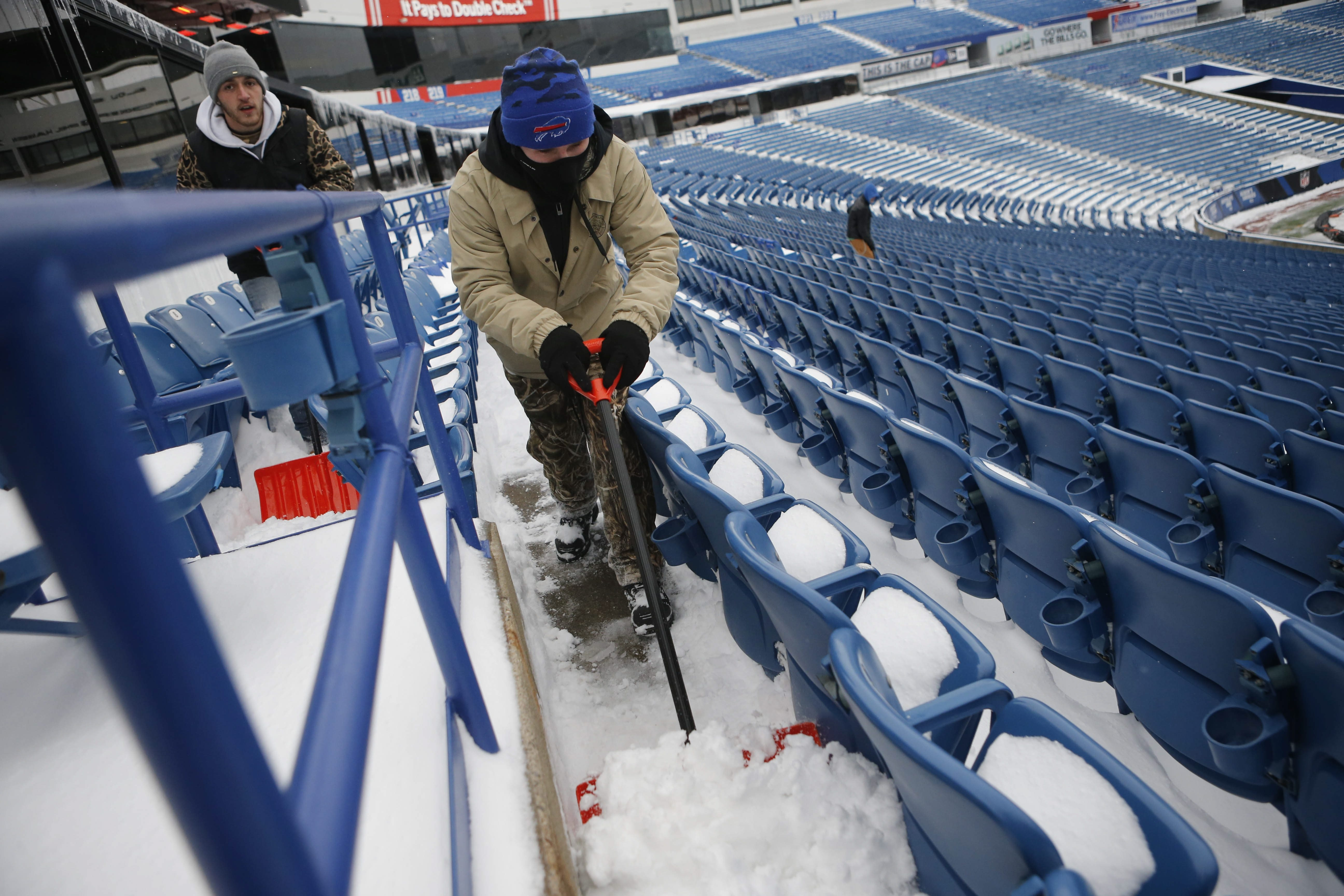 A shovel brigade clears snow from the stands at Ralph Wilson Stadium ahead of tomorrow's season closer against the Jets, Saturday, Jan. 2, 2016.  (Derek Gee/Buffalo News)