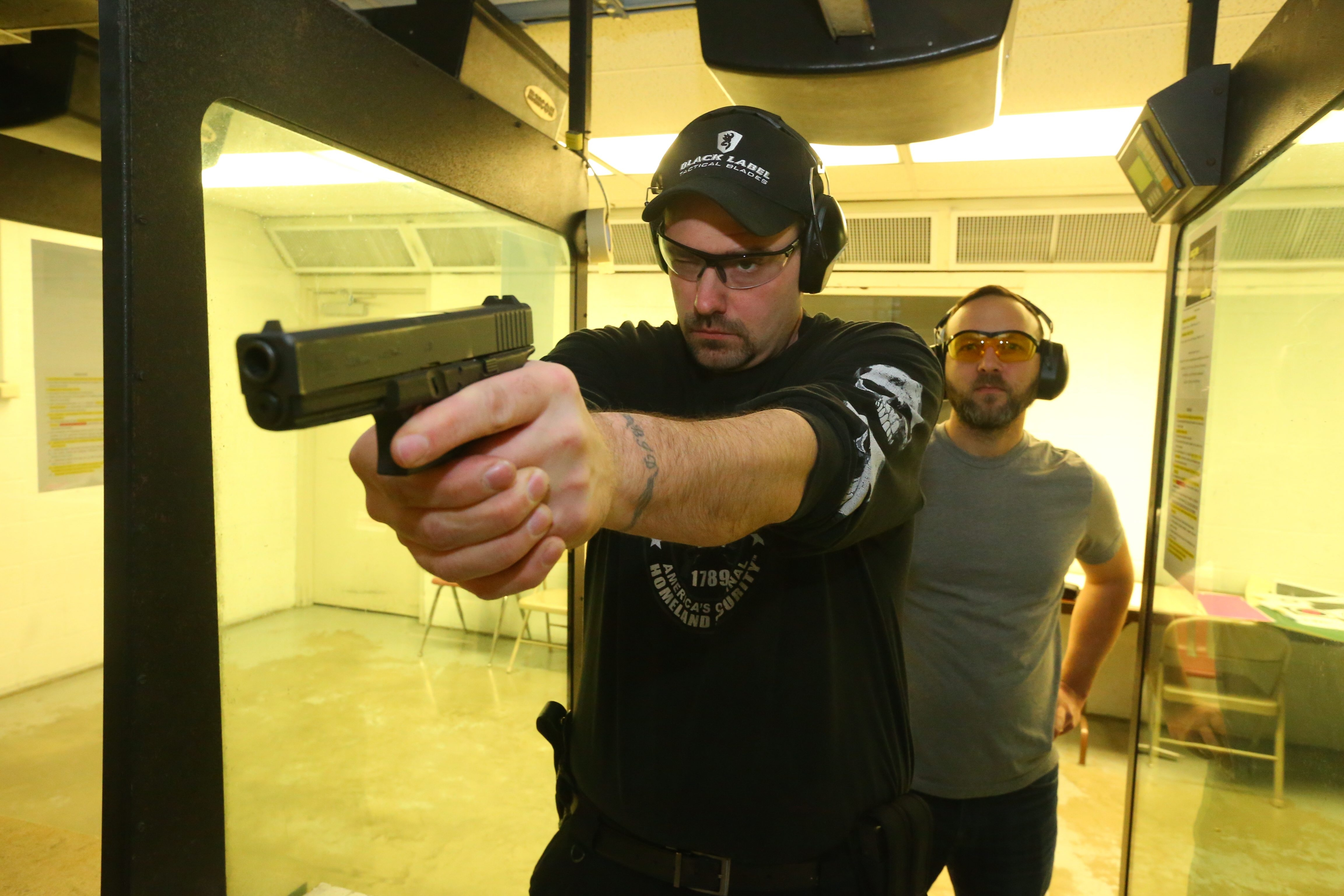Michael Deasy, right, co-owner of Niagara Gun Range, is shown at the shooting range area with pistol permit holder and employee Luke Price. Besides shooting in the gun range, customers can also buy firearms and receive handgun safety training there. (John Hickey/Buffalo News)