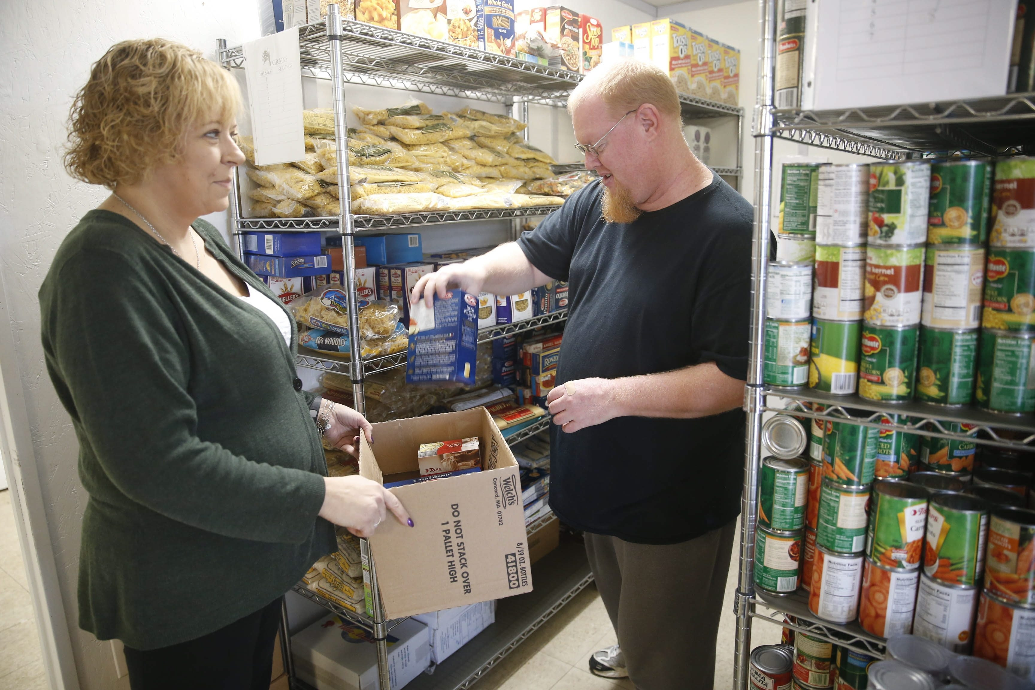 Administrator Joanne Whitney, left, and volunteer Robert Montgomery unpack supplies onto the shelves at the Care-n-Share Food Pantry in Ransomville, which feeds more than 200 families per month.