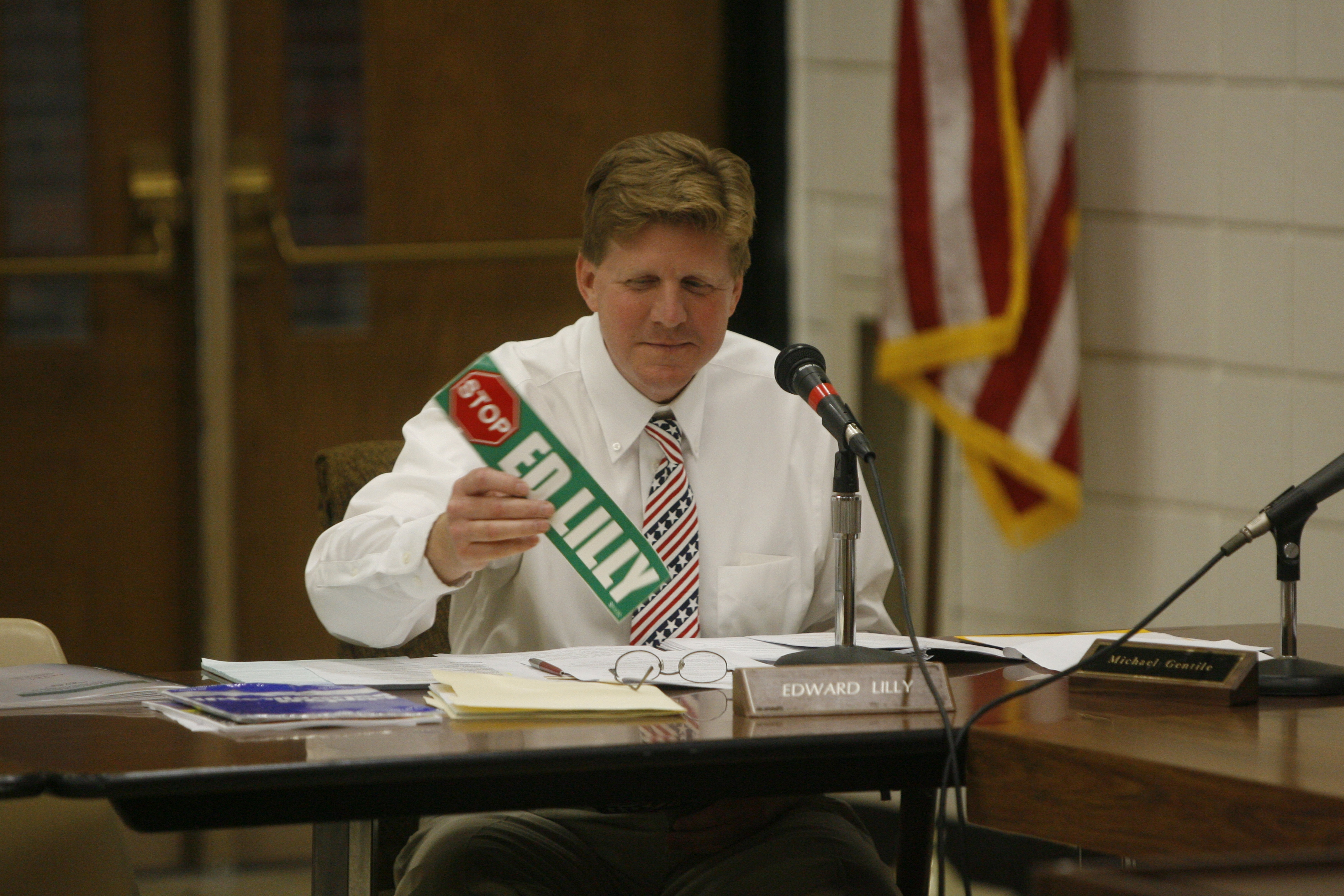 Ousted Lew Port School board member Edward Lilly looks at a bumper sticker a community activist gave him as a going-away present.  (Robert Kirkham/Buffalo News file photo)
