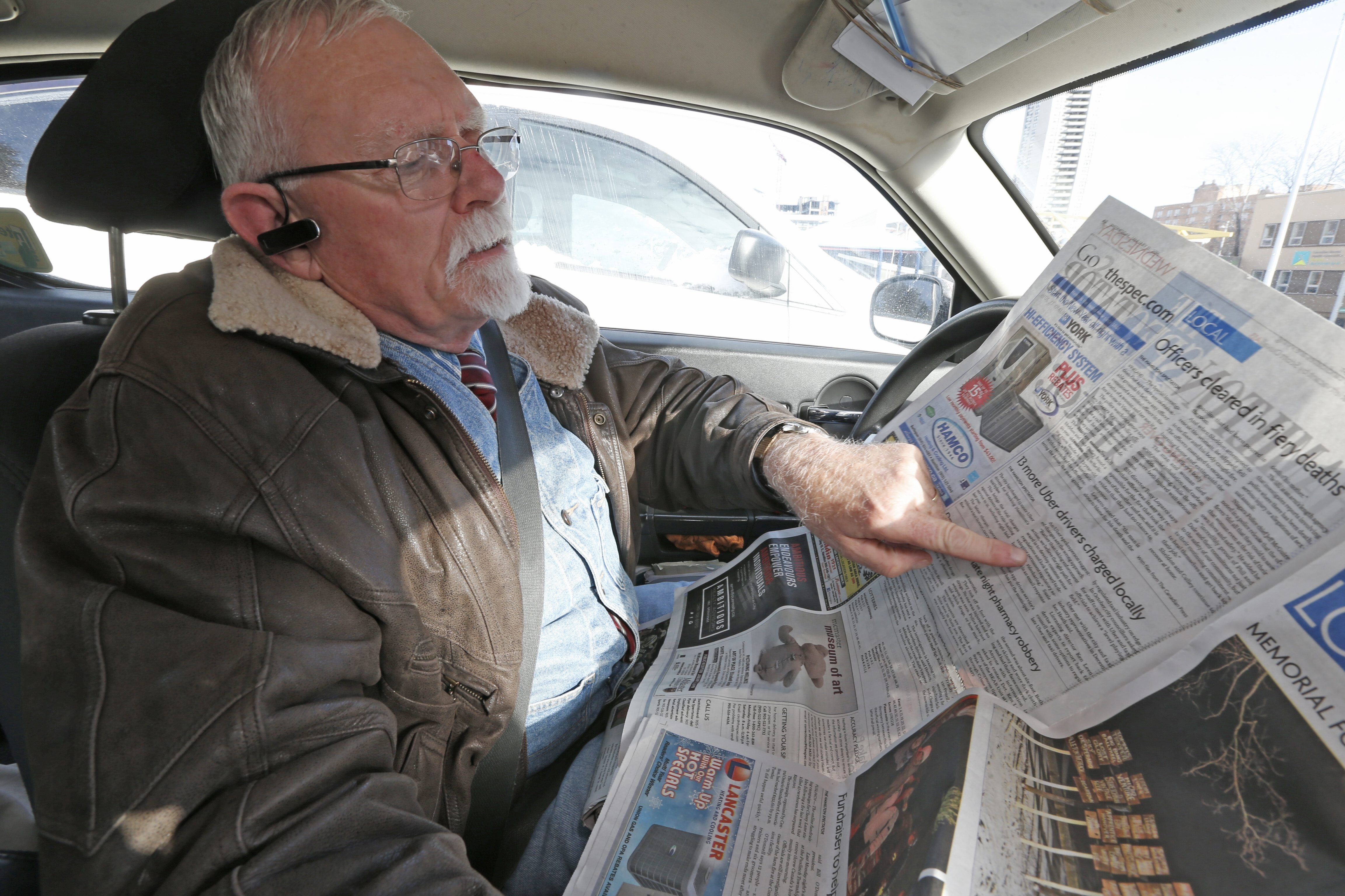 In Hamilton, Ont., cab driver Bill Cranston points out a headline in the Hamilton Spectator that said that Uber drivers had been charged for not having taxi licenses.