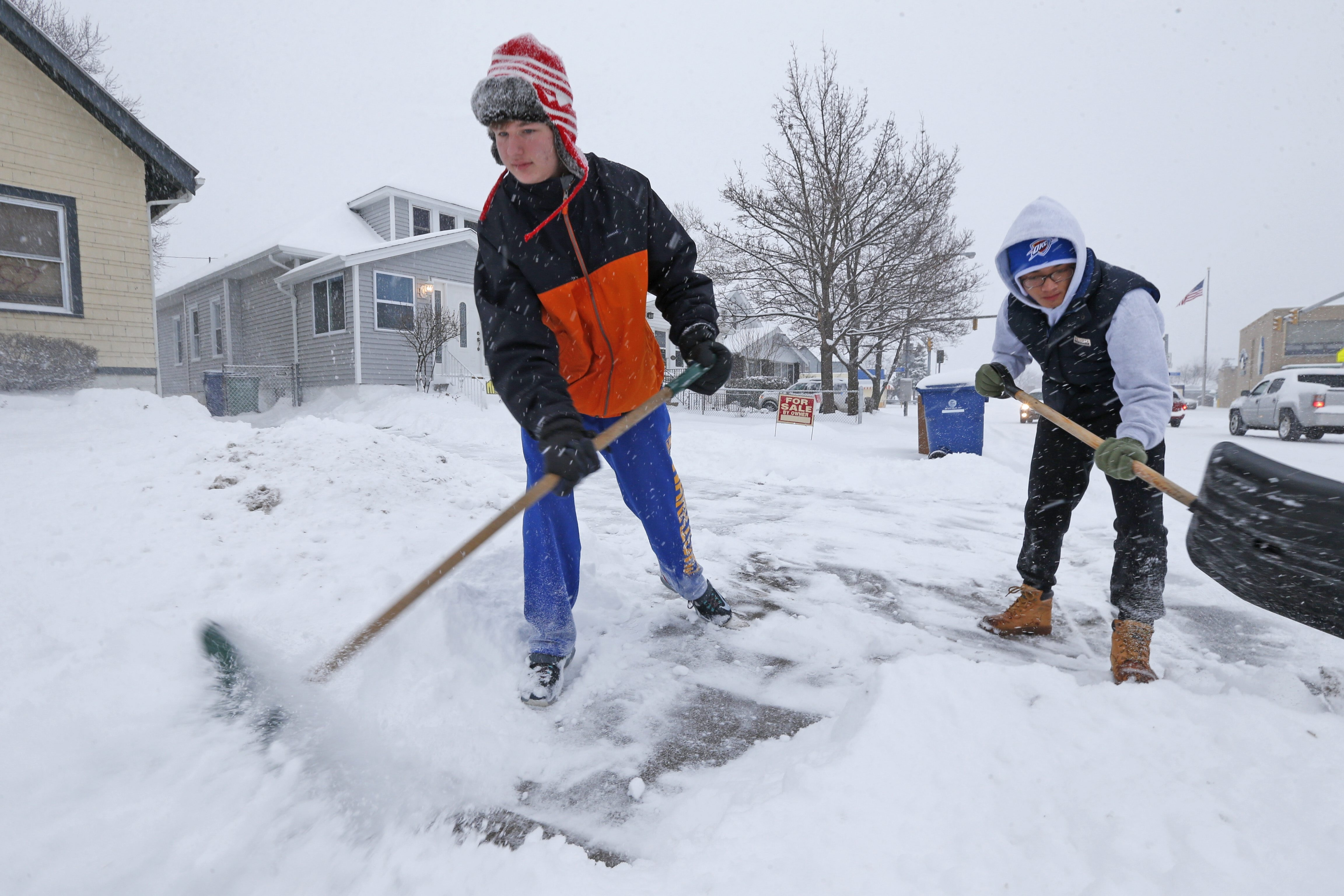 Joe Snyder, 16, left, and his brother Benny Yu, 17, try to keep up with the snow outside their Abbott Road home in Buffalo, where 5 to 6 inches fell on Sunday.