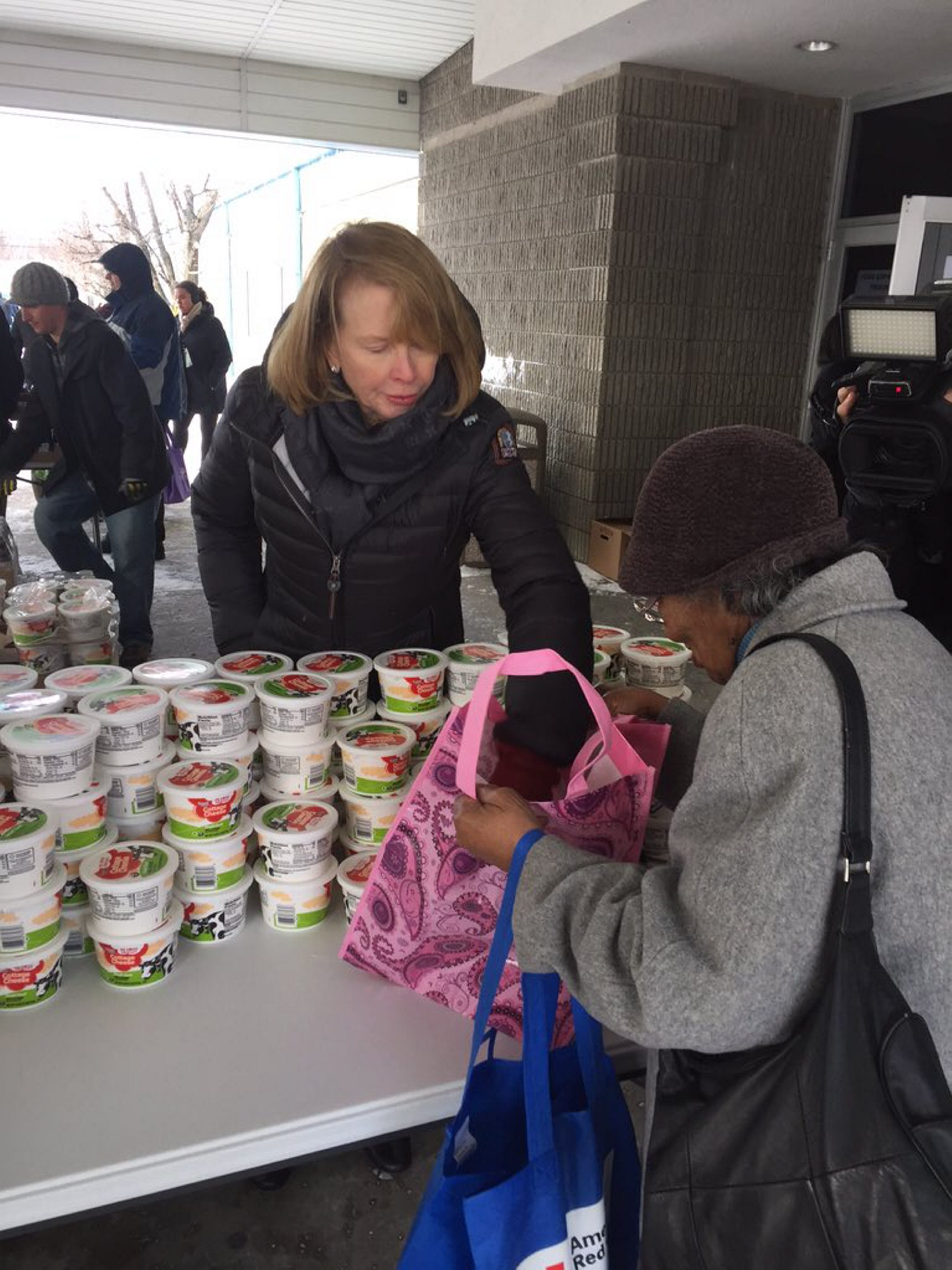 Mary Wilson hands out food at Resurrection Life Food Pantry in Cheektowaga after giving a $500,000 grant to the Food Bank of Western New York.