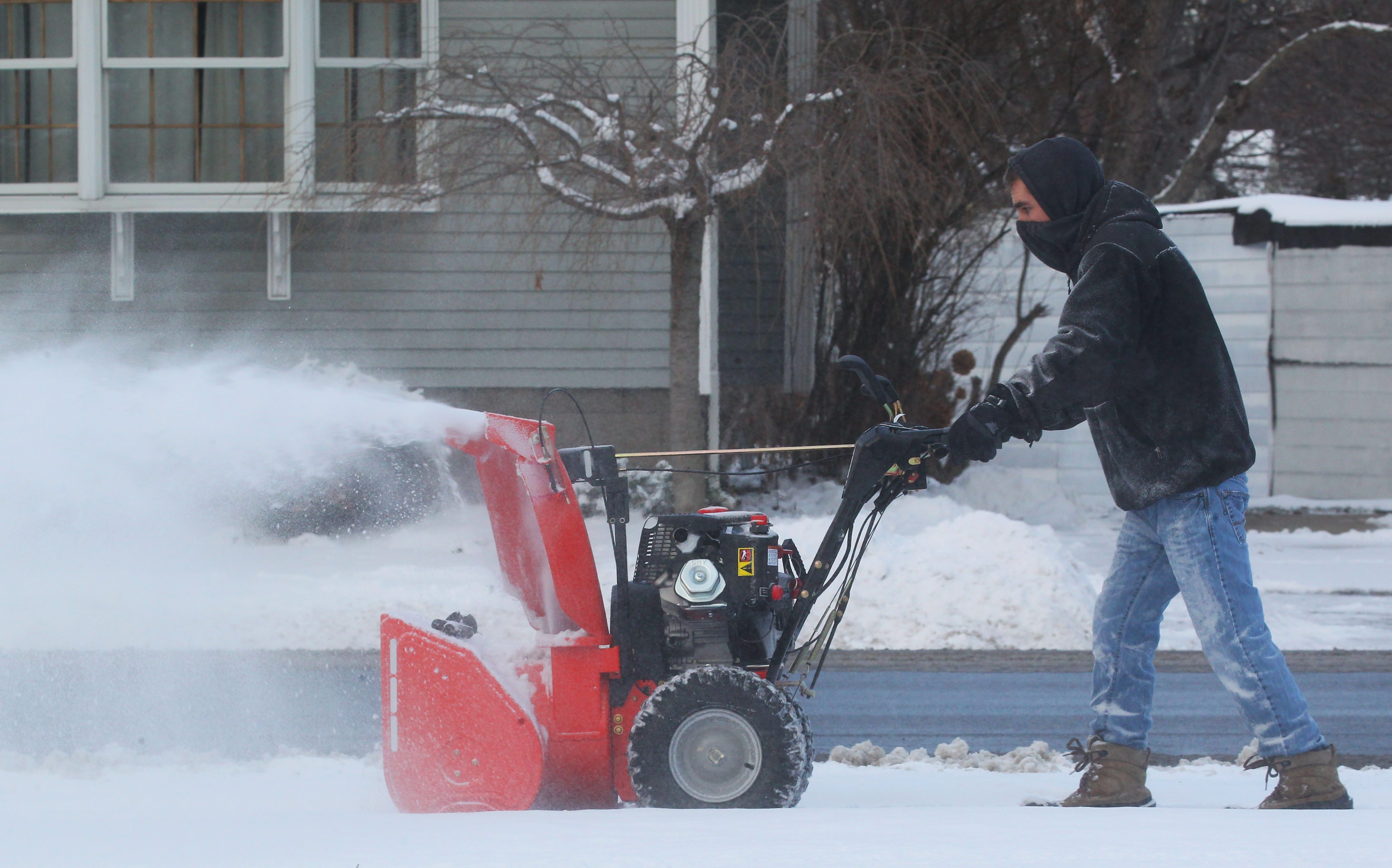 Joe Marcaccio clears the sidewalk at the City of Tonawanda Public Library on Monday.  The lake-effect snow bands are expected to move out of the area Tuesday.