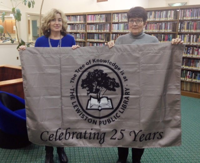Director Jill Palermo left, and JoAnne Lotterio hold an anniversary banner for the Lewiston Public Library.
