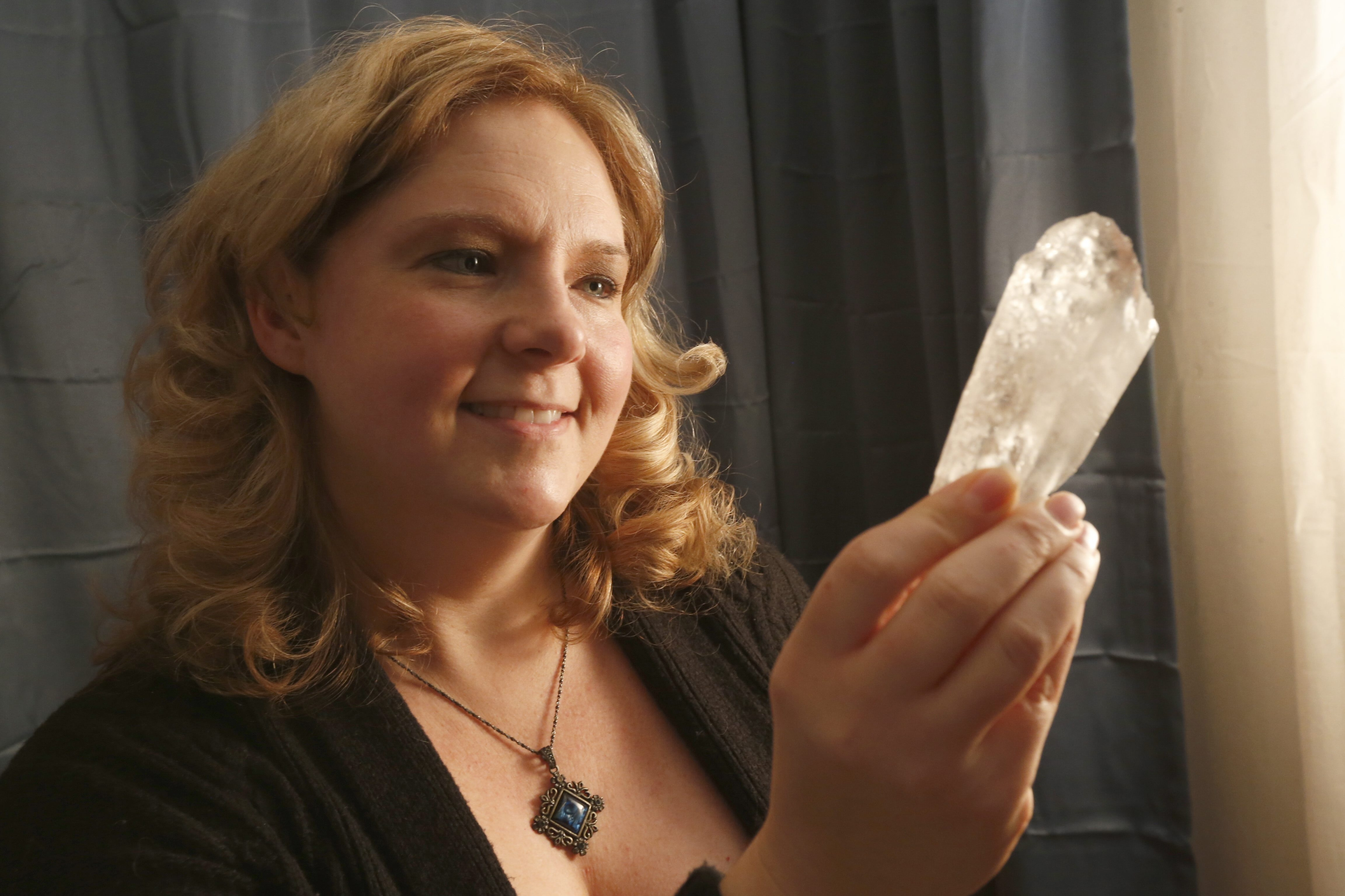 The Rev. Dr. Pamela Bruns gazes into a quartz healing stone at Spiritually Rooted II, her new location in Lewiston.