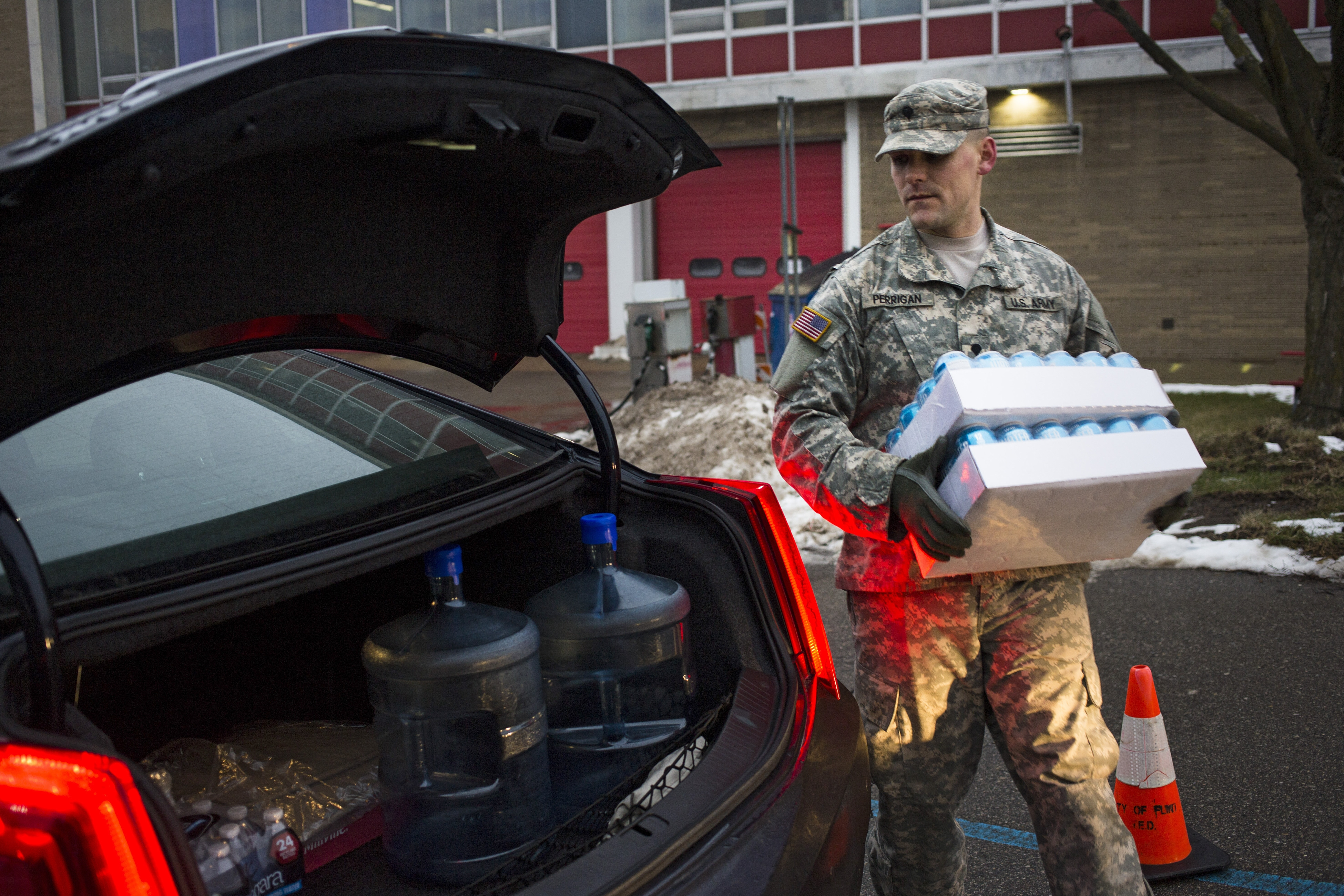 The national Guard is helping distribute water in Flint, Mich. Here, Spc. Eric Perrigan loads cases of water into a resident's car at a Flint fire station. (New York Times photo)