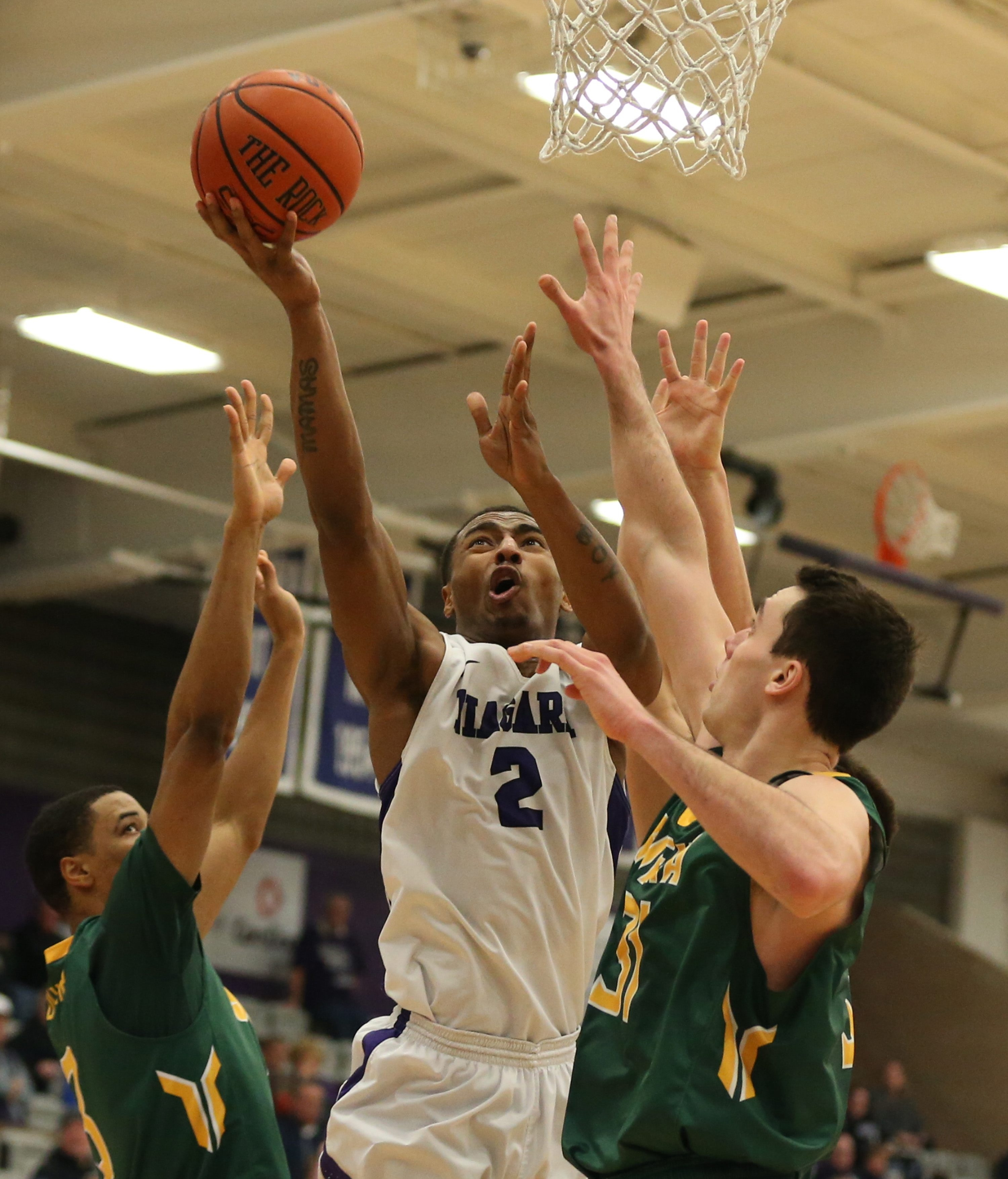 Niagara's Emile Blackman drives to the basket on Siena's Brett Bisping, right, in the second half.
