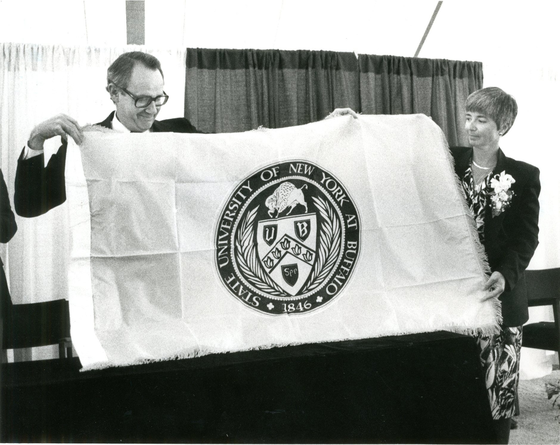 Marcia Jarvis returns the flag her late husband, Gregory, took aboard the ill-fated space shuttle Challenger to UB President Steven B. Sample. Oct. 12, 1987.  (News file photo)