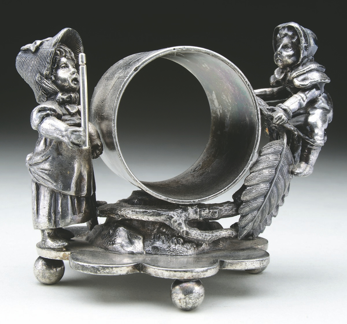 "Kate Greenaway drawings inspired this silver-plated ""double Greenaway"" figural napkin ring made by Simpson, Hall, Miller & Co. It brought $533 at auction."