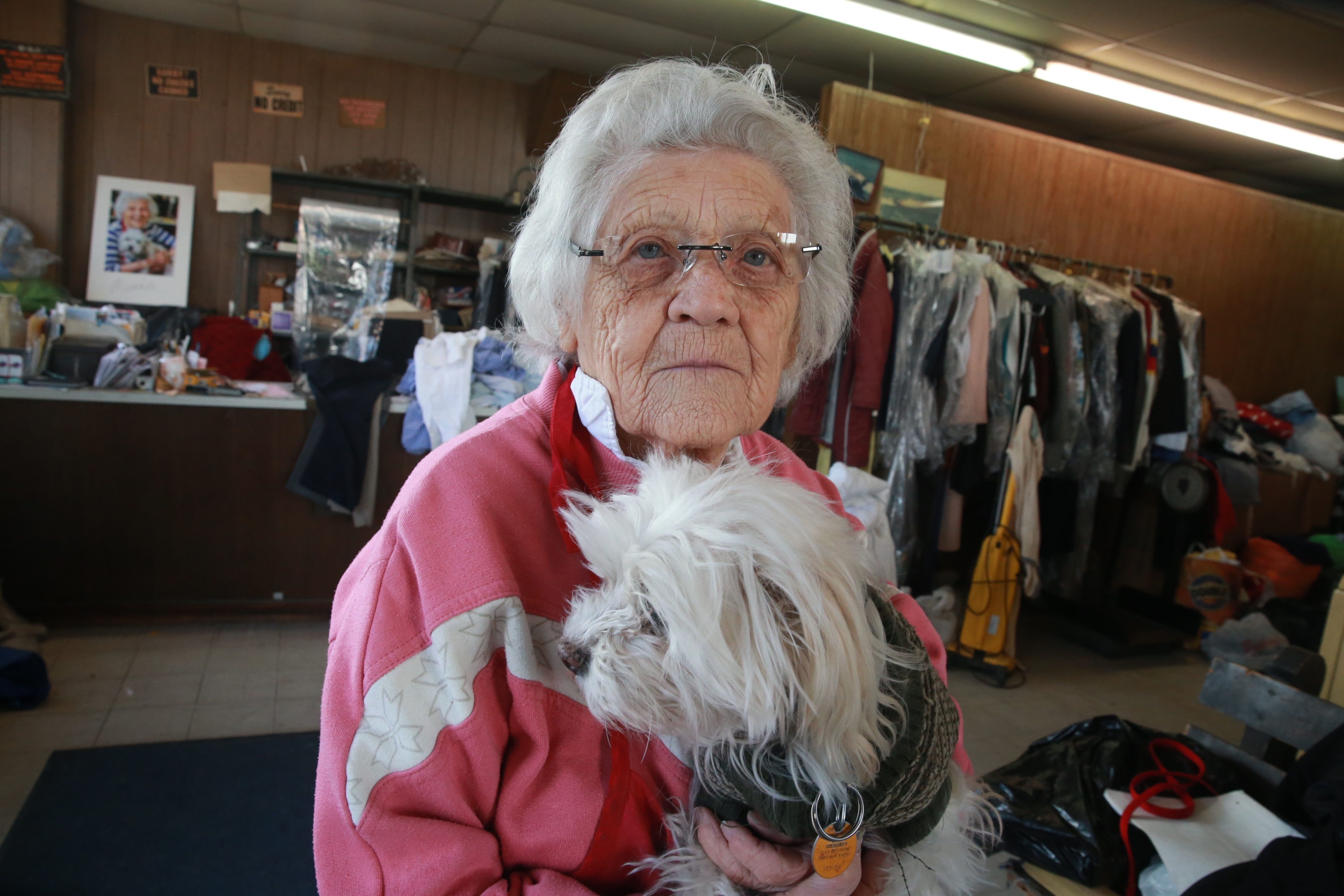 """One hundred-year-old Felimina """"Minnie"""" Rotundo holds Benji, her best friend, at her College Laundry Shoppe on Main Street in the University District. She still works 10 hours a day, six days each week and is looking forward to her 101st birthday in August, which she'll celebrate at her summer cottage in Angola."""