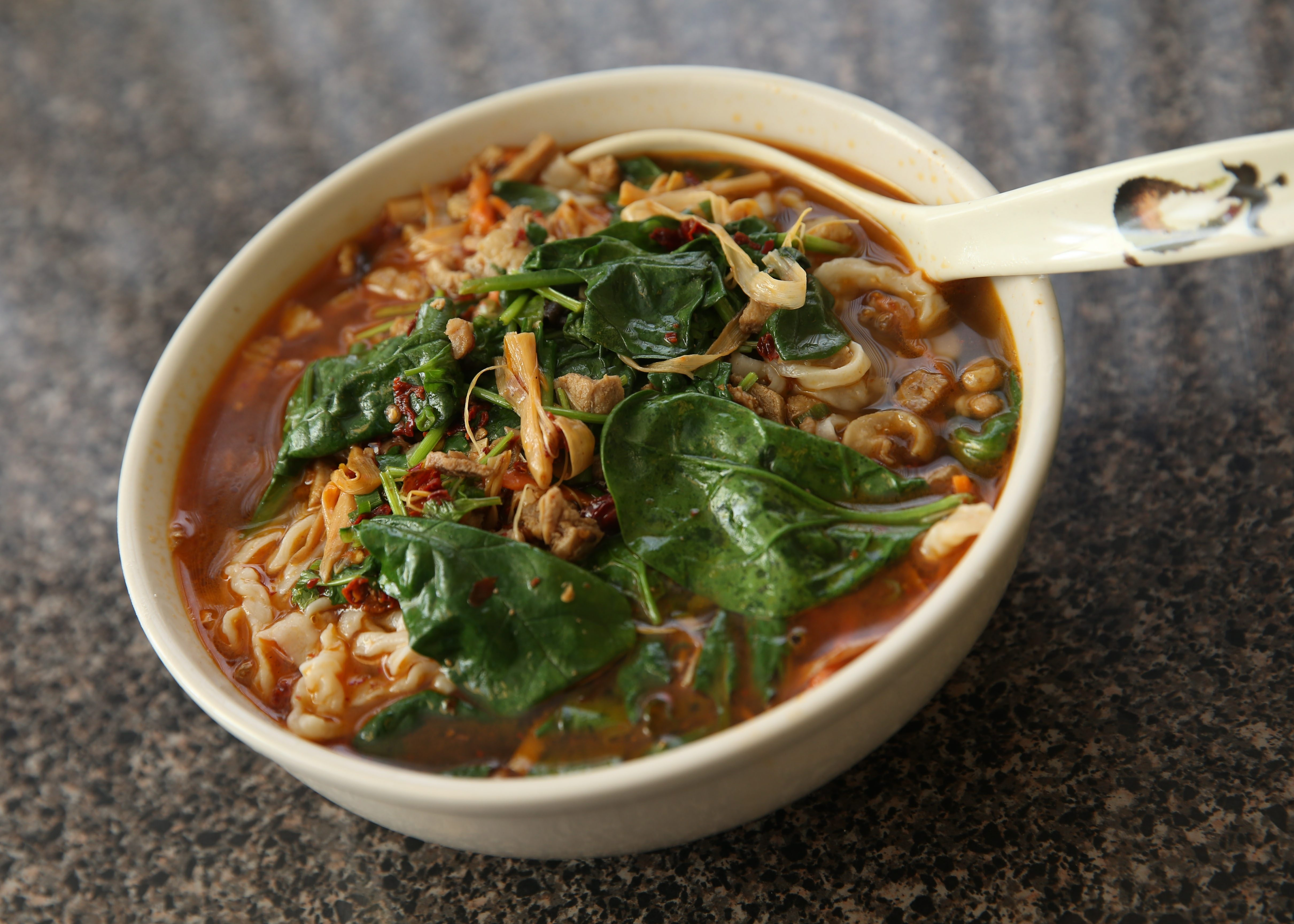 Noodles in a bit of spicy chile-laced broth, tangy with vinegar, and a jumble of vegetables