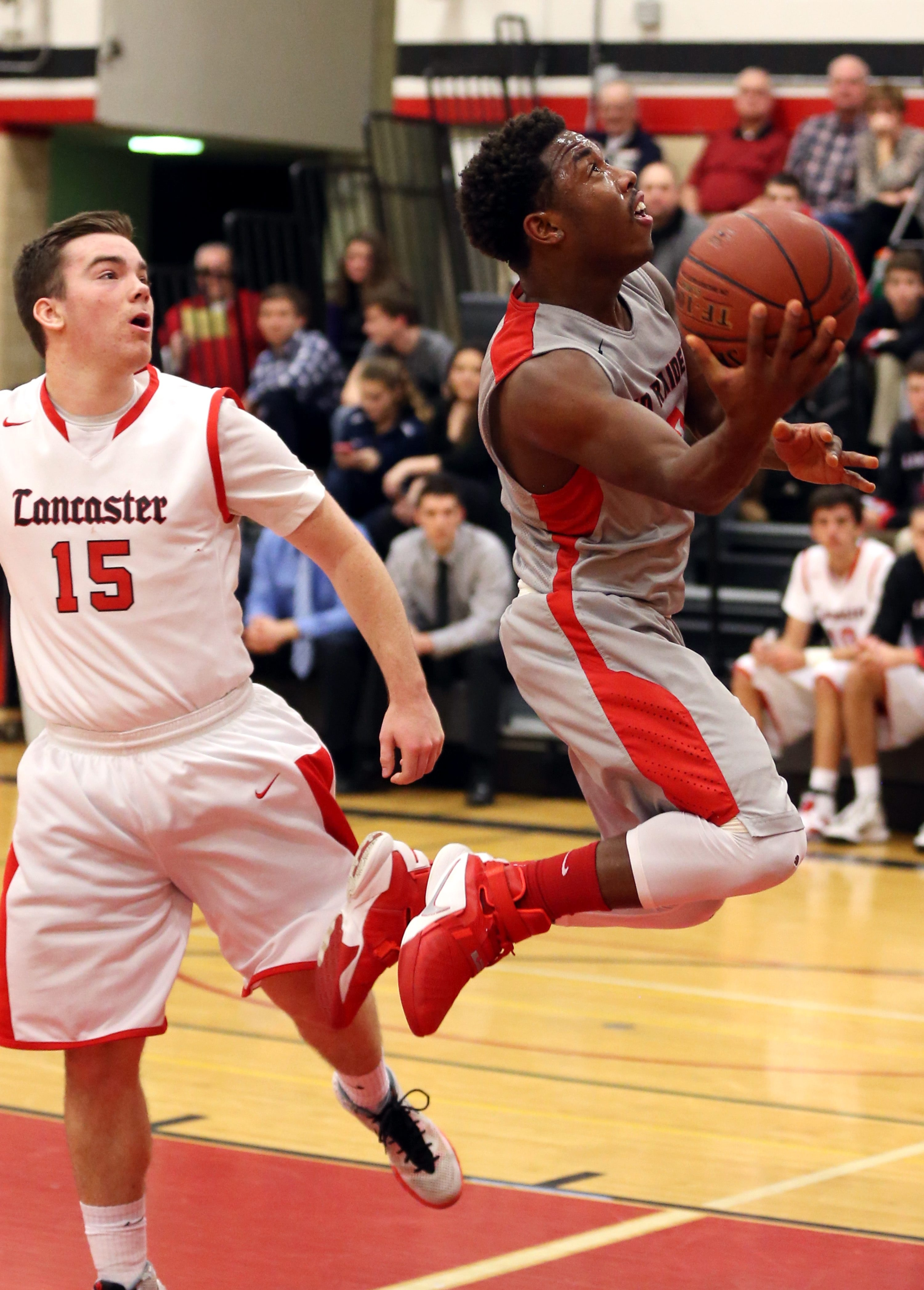 Jamestown's Zacc Kinsay scores two points  against lancaster's Sean Gill in the second quarter at Lancaster High School in Lancaster, NY on Monday, Jan. 25, 2016.  (James P. McCoy/ Buffalo News)