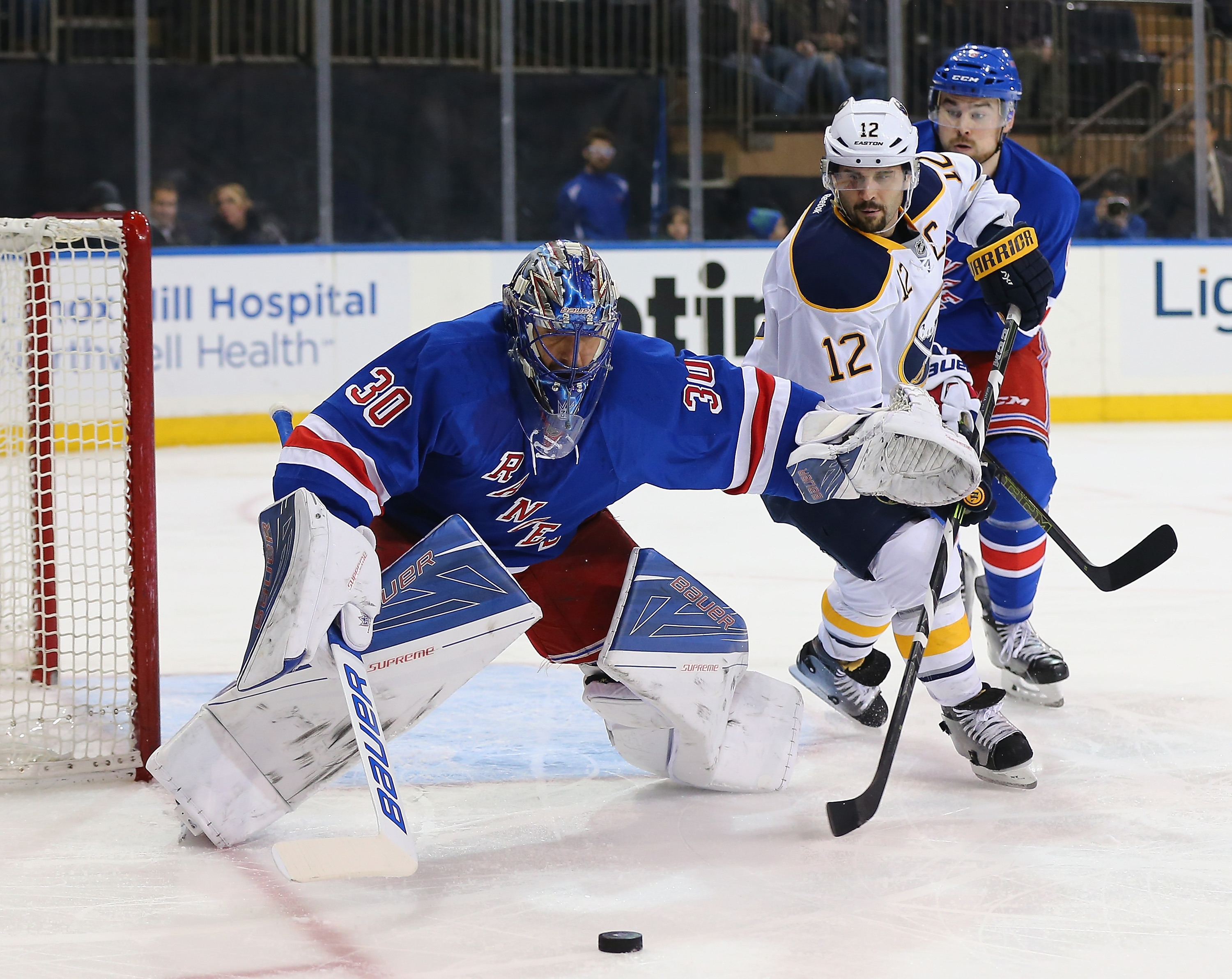 Rangers goalie Henrik Lundqvist tries to keeps Sabres captain Brian Gionta away from a rebound at Madison Square Garden.