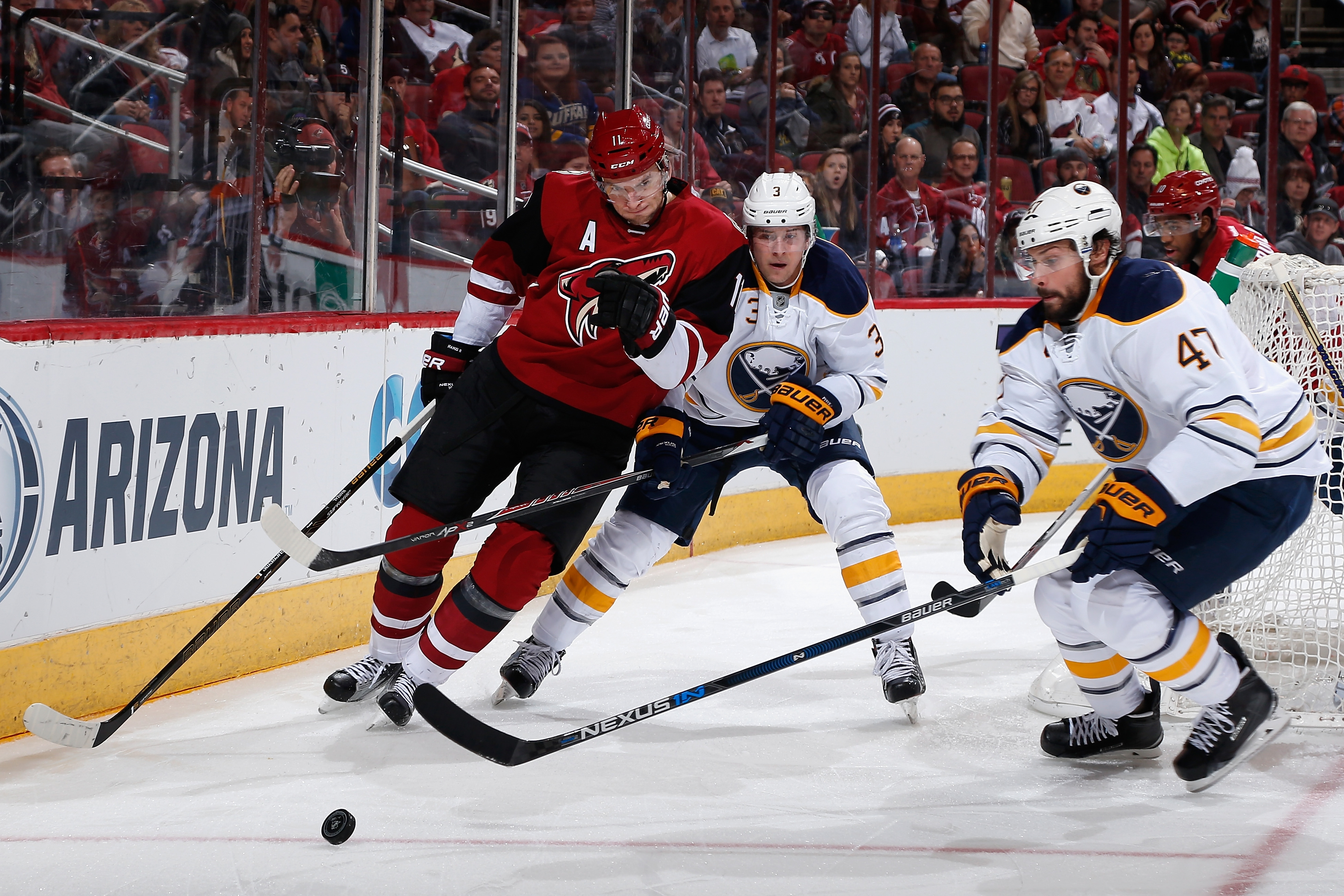 Zach Bogosian (47) looks to clear the puck while teammate Mark Pysyk contains the Coyotes' Martin Hanzal during the first period Monday night.