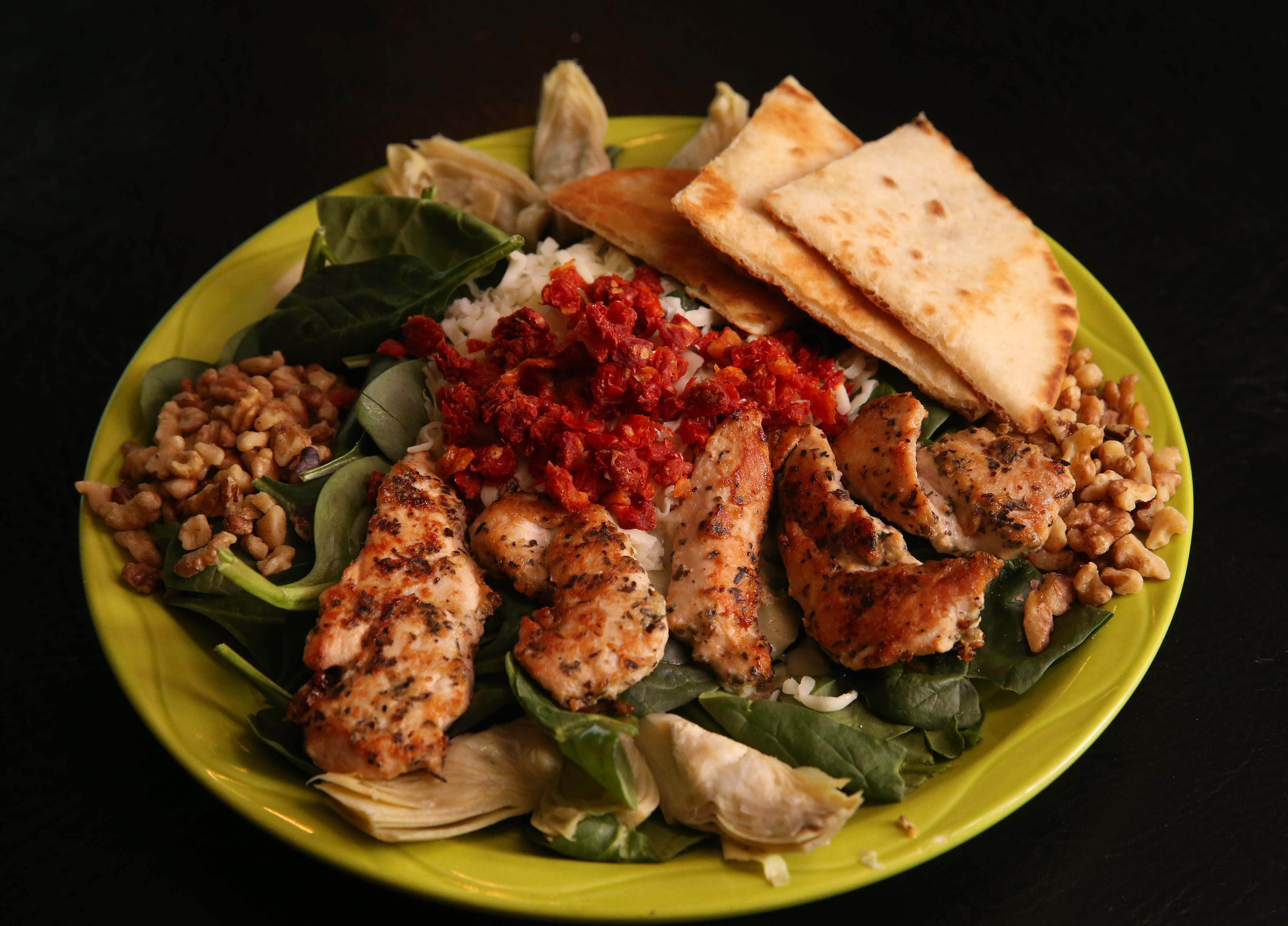 Salad is made with spinach, marinated chicken, mozzarella cheese, artichokes, walnuts and sun-dried tomatoes.
