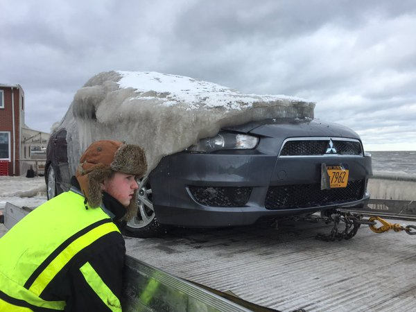 A crew from Lake Erie Towing & Recovery  is taking the 'ice car' away from Hoak's to a collision shop. (Aaron Besecker/Buffalo News)