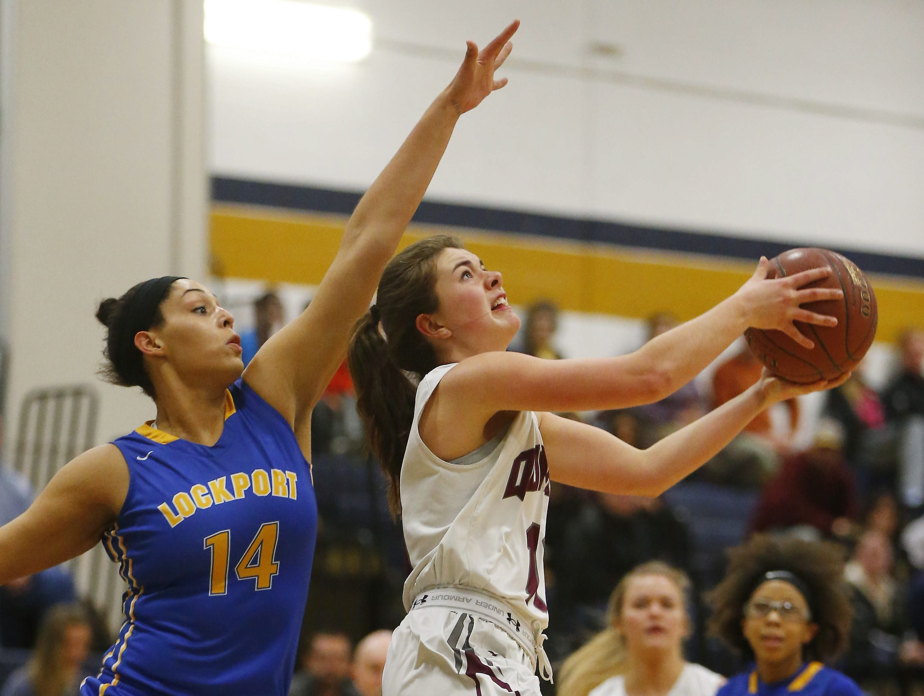 Orchard Park's Jaimee Glendenning drives to the hoop on Lockport's Brooklyn Camarra in the first half of their Class AA semifinal at Sweet Home on Friday. The Quakers earned a 61-41 win.