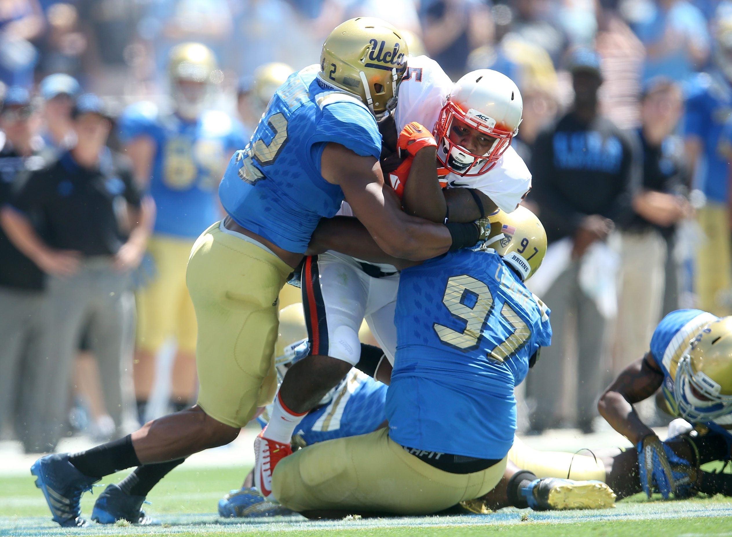 UCLA defensive lineman Kenny Clark, right, tackles Virginia running back Albert Reid. Clark says his tough childhood made him a better football player.