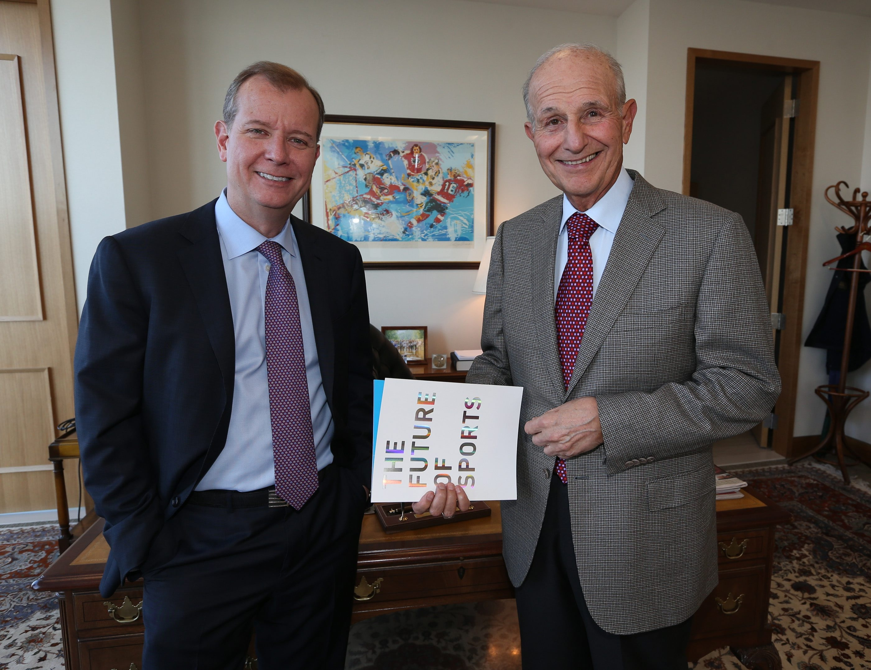 Jeremy Jacobs and his son, Jerry Jacobs Jr., hold the book they had commissioned to take a look at sports 25 years down the line in their Buffalo office at Delaware North.