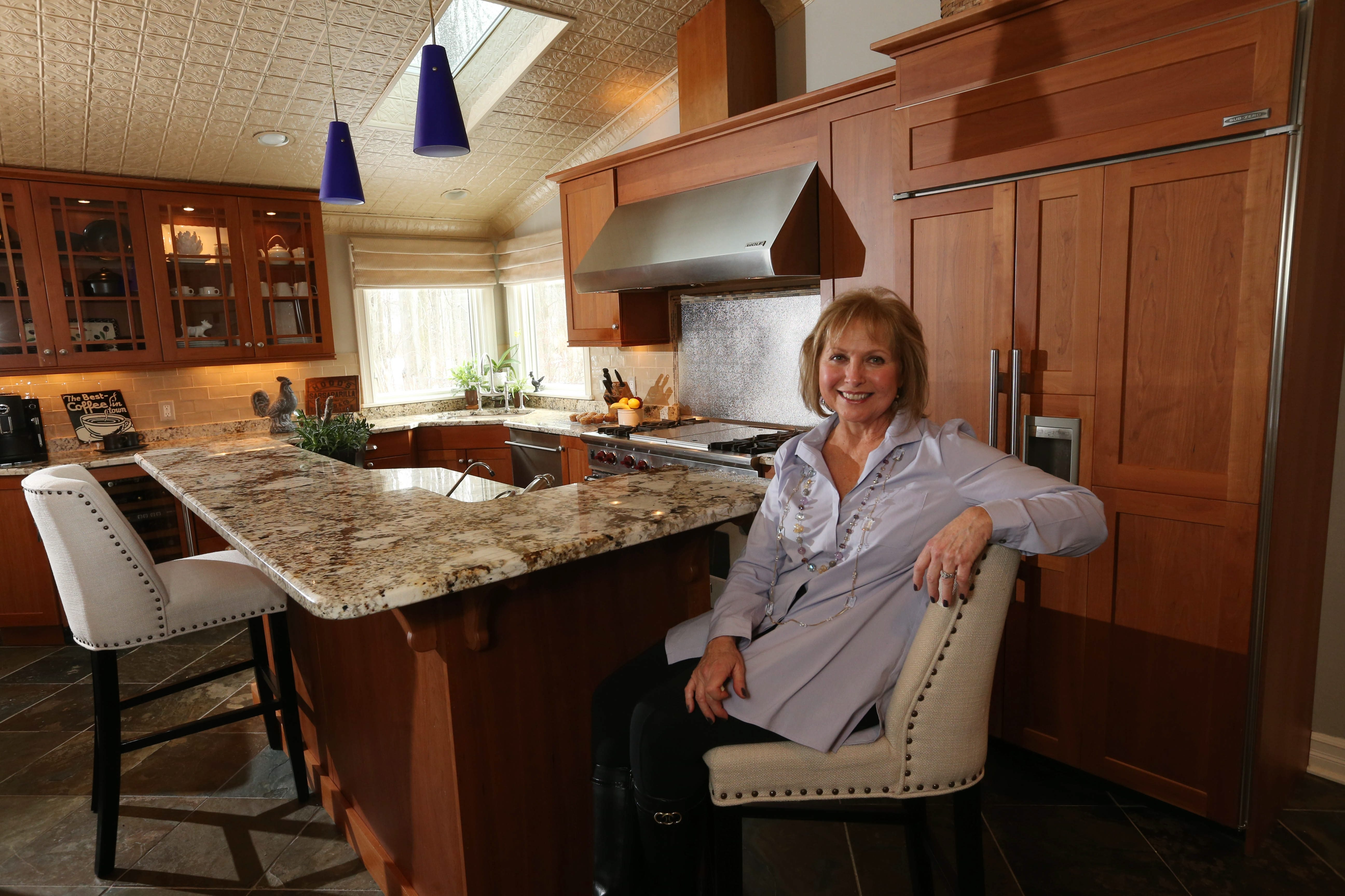 Susie Riessen sits at the two-level island in her East Amherst kitchen. Highlights include granite countertops, cabinets in a medium-cherry finish and a sloped, painted tin ceiling.