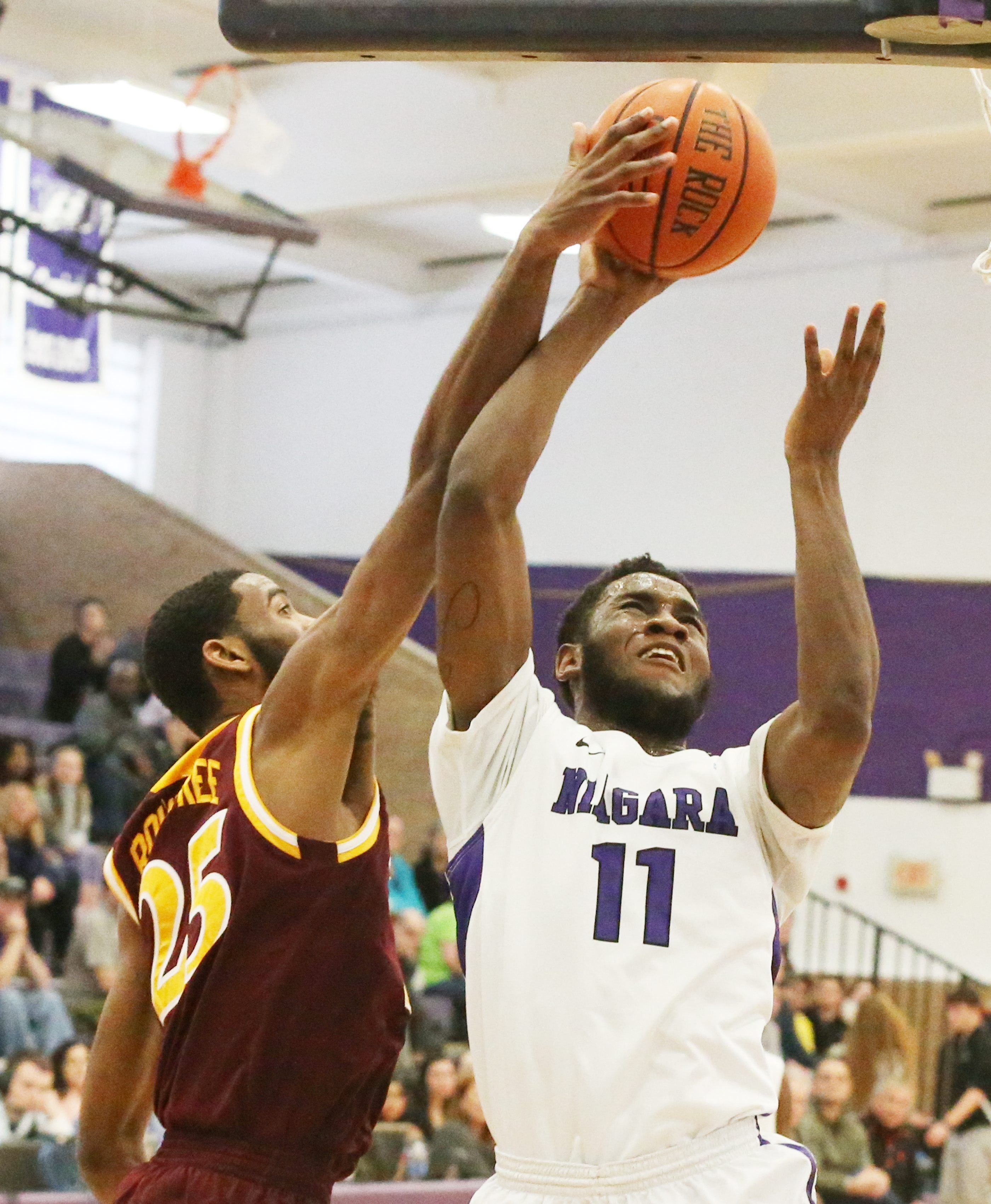 Niagara forward Marvin Prochet is fouled by Iona forward Aaron Rountree Sunday at the Gallagher Center.