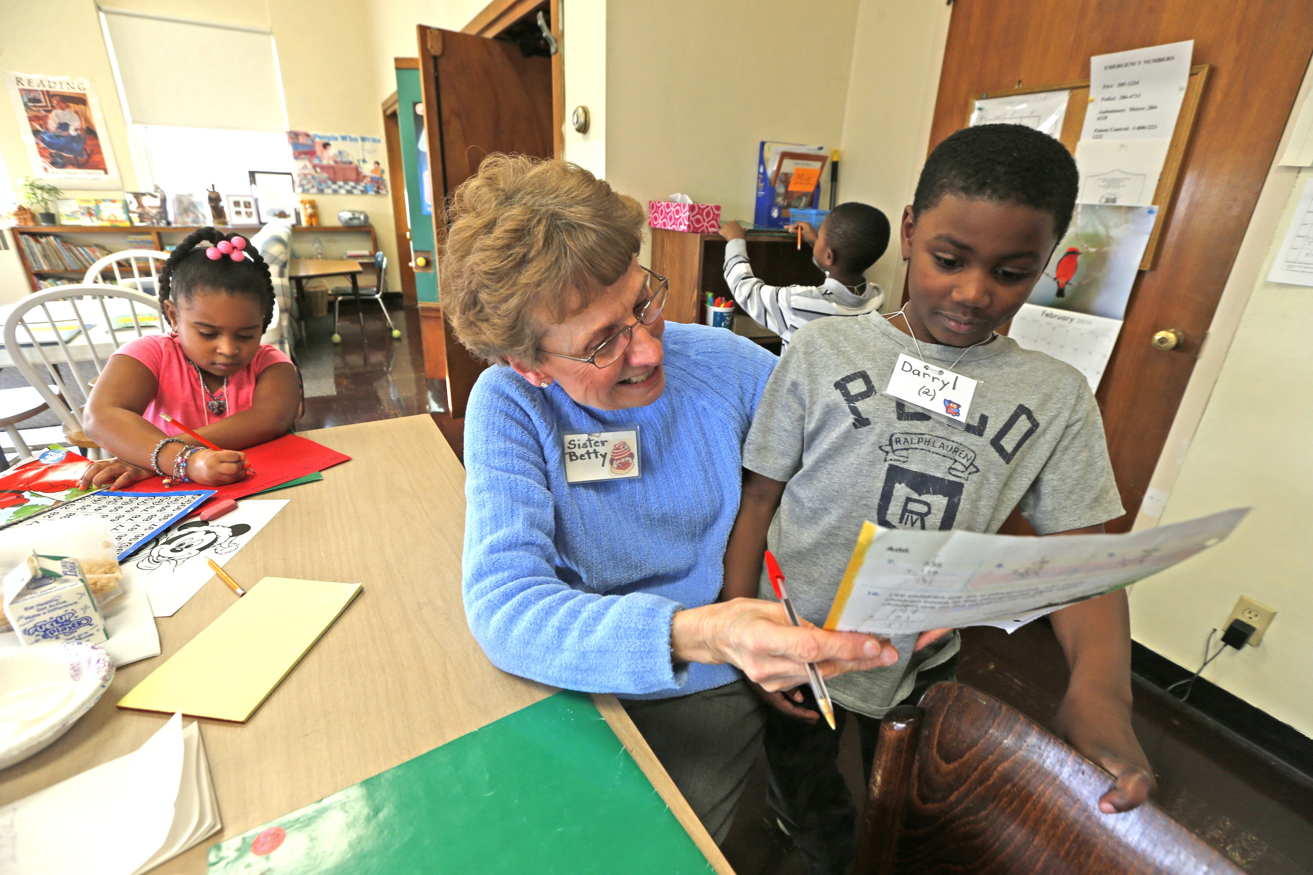 Sister Betty Neumeister helps Darryl Smith, 7, with his math homework at the Francis Center Children's Program in a former Catholic school in Niagara Falls. The program helps students with academics through one-on-one tutoring.