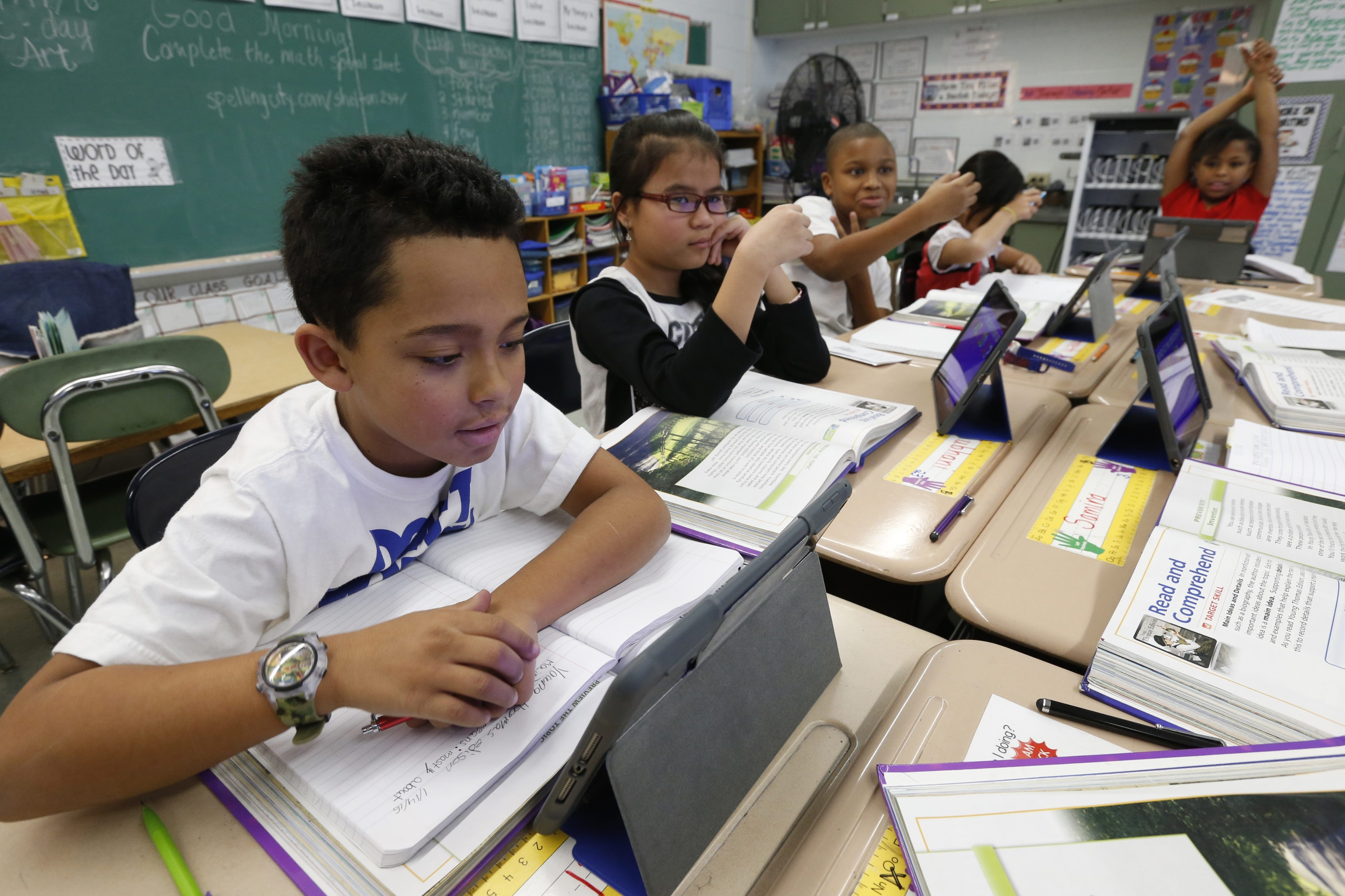 Third graders at Buffalo Elementary School of Technology, including Michael Mingle, left, work with their iPads during class last month.