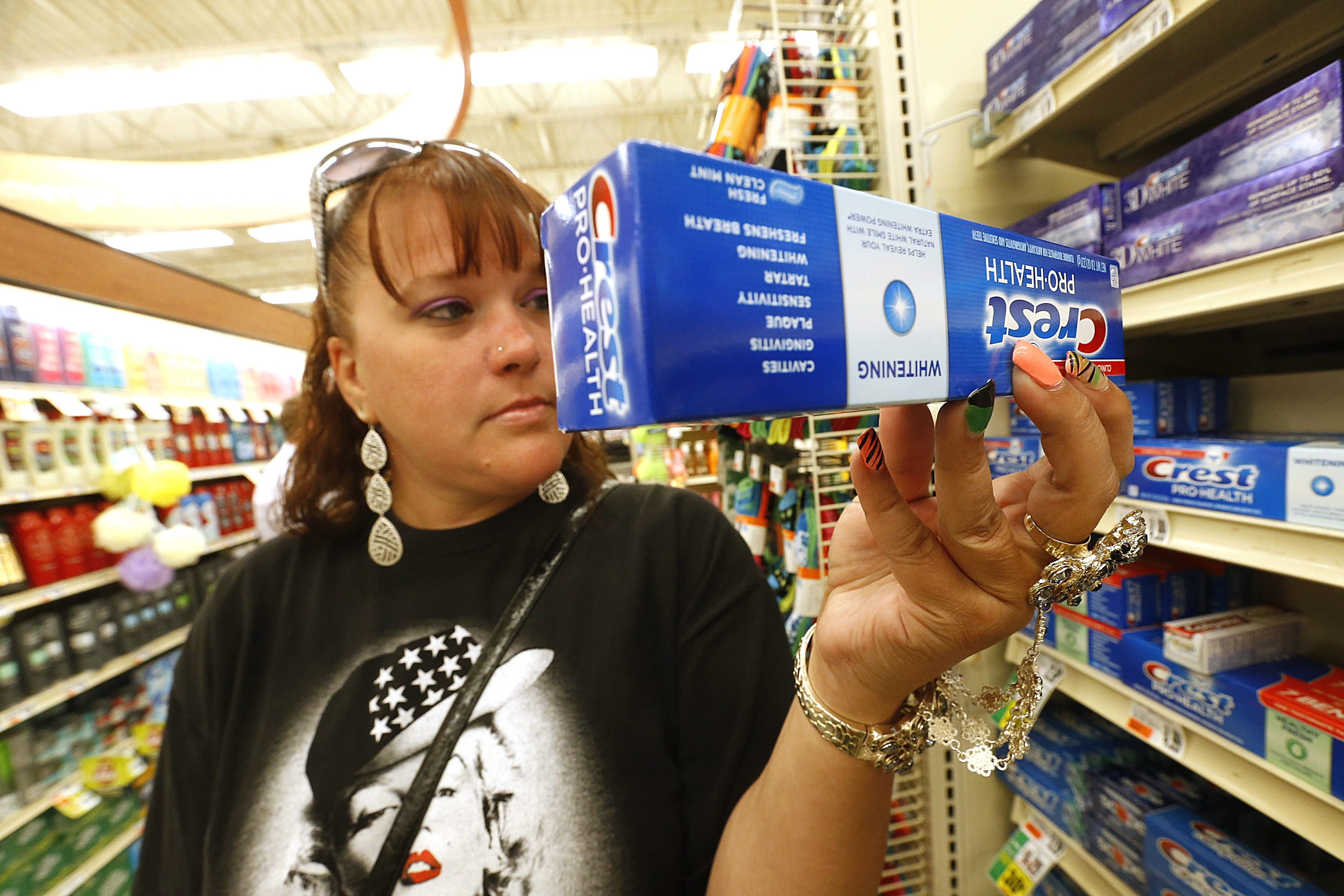 Jennifer Horn of Buffalo, stops for a moment from shopping to read the ingredients on a box of toothpaste. Many of the high end toothpastes contain tiny microbeads, like these being offered at Tops Friendly Markets on Amherst St. in Buffalo on Tuesday, Aug. 11, 2015.  (Robert Kirkham/Buffalo News)