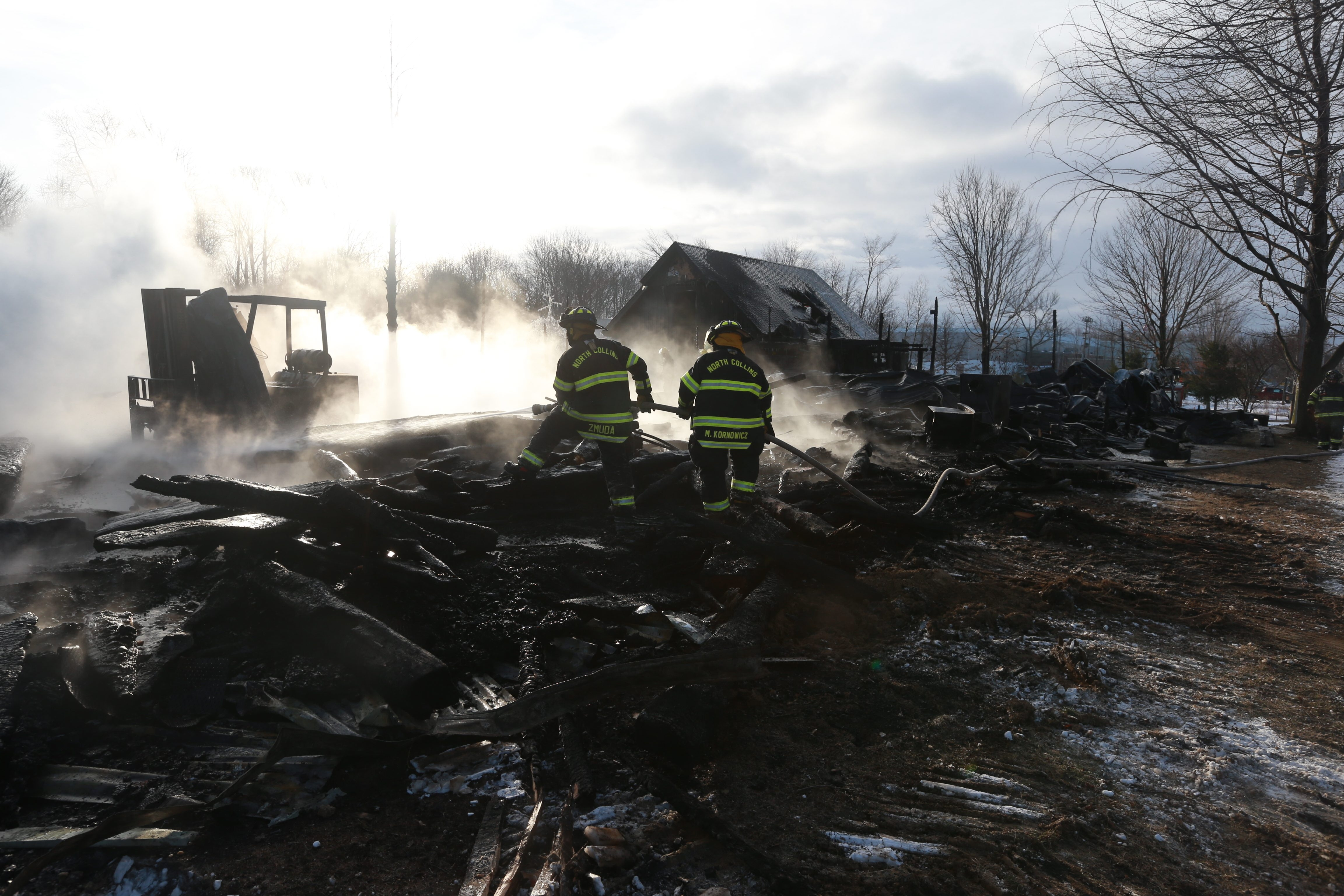 North Collins firefighters extinguish the remains of a three-alarm blaze at the Timberbuilt shop in North Collins on  Thursday,  Feb. 11, 2016.   (John Hickey/Buffalo News)