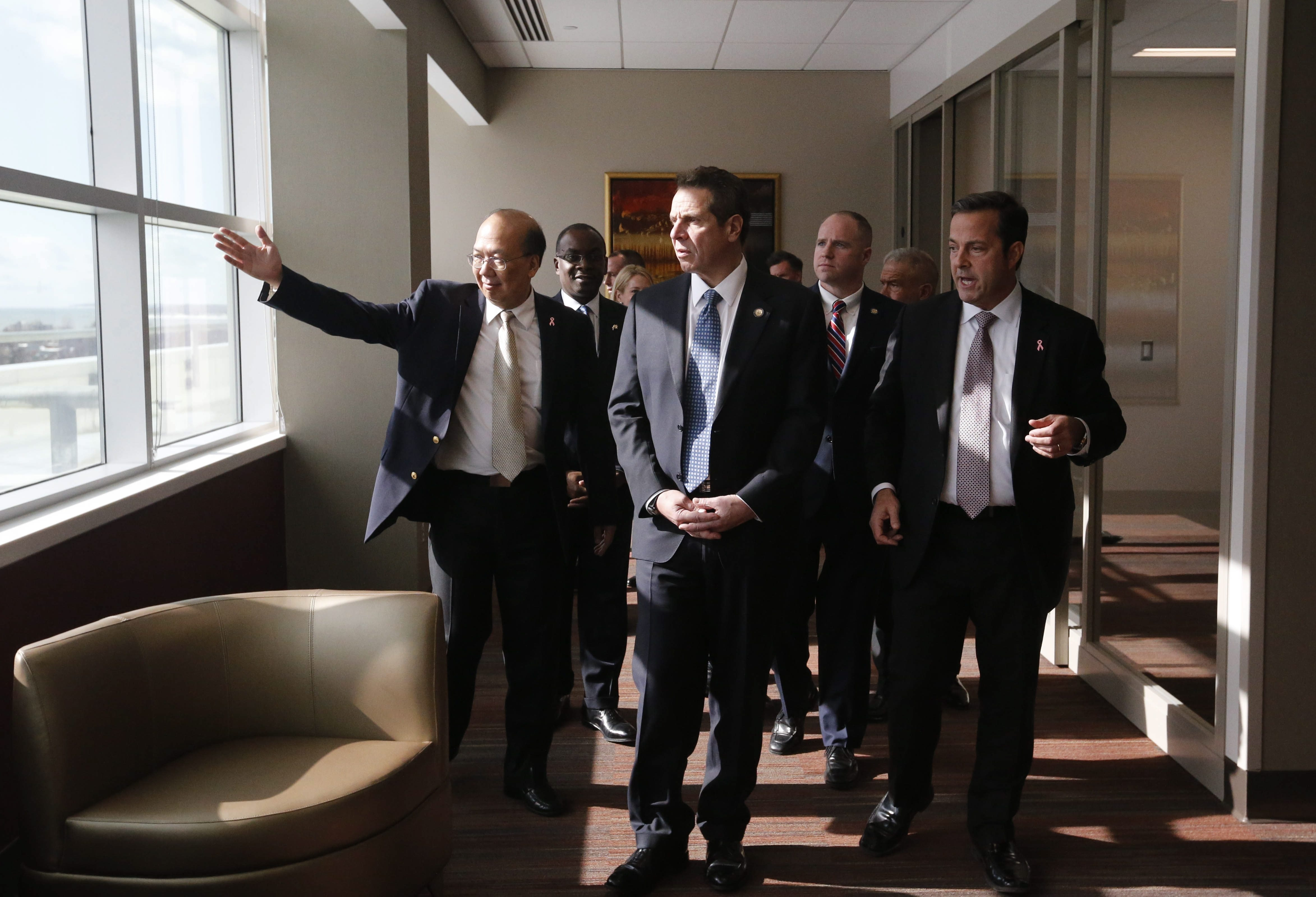 Gov. Andrew Cuomo, center, tours the new Athenex facility at Conventus in Buffalo with Athenex CEO Johnson Y. N. Lau, left, and CFO and COO Flint D. Besecker, right, Thursday, Feb. 11, 2016.  (Derek Gee/Buffalo News)