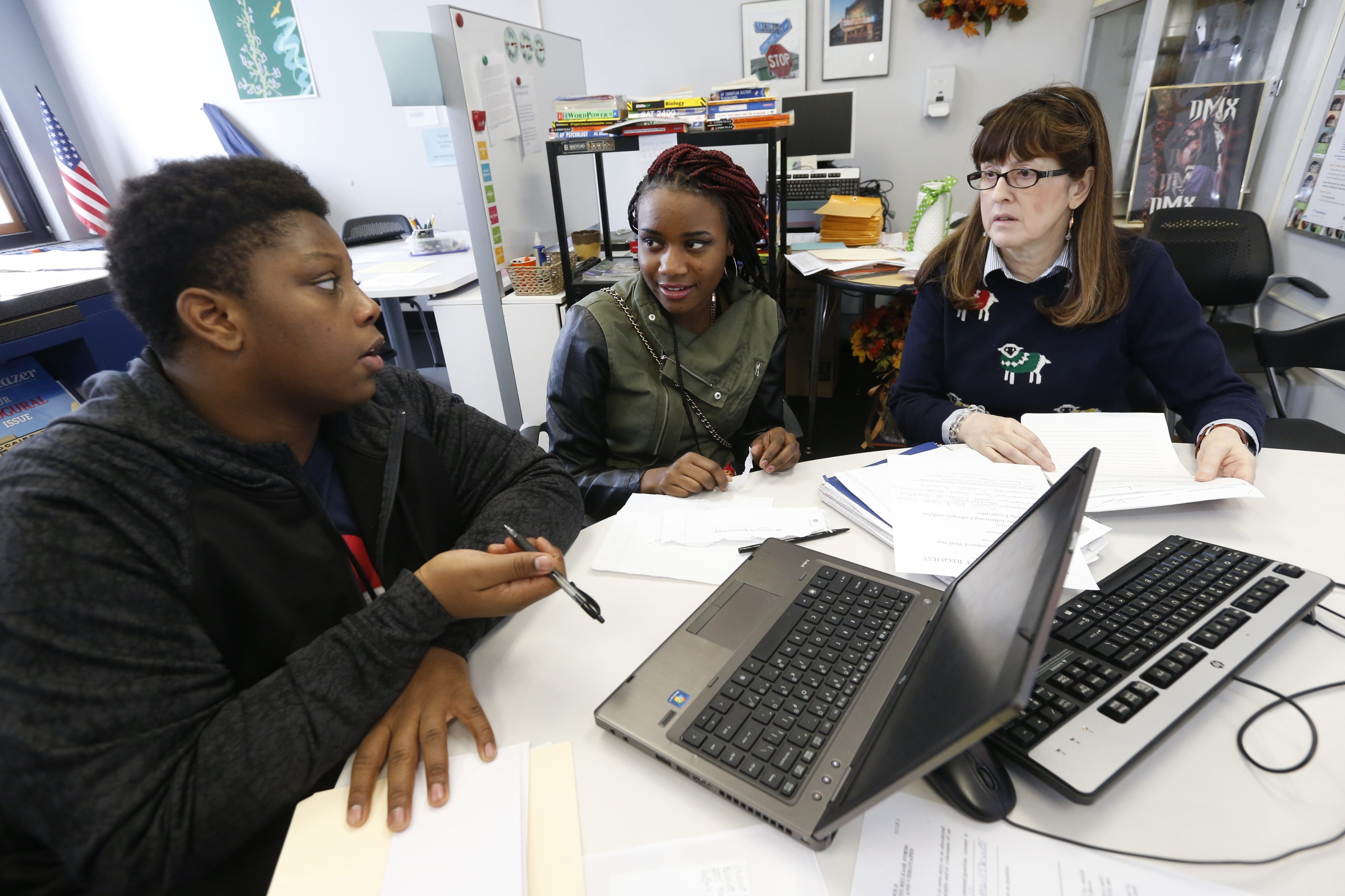 From left, Bennett High School seniors Eugene Steele and Shaniyah Crump discuss the college application progress with school counselor Maureen England in the College Success Center.