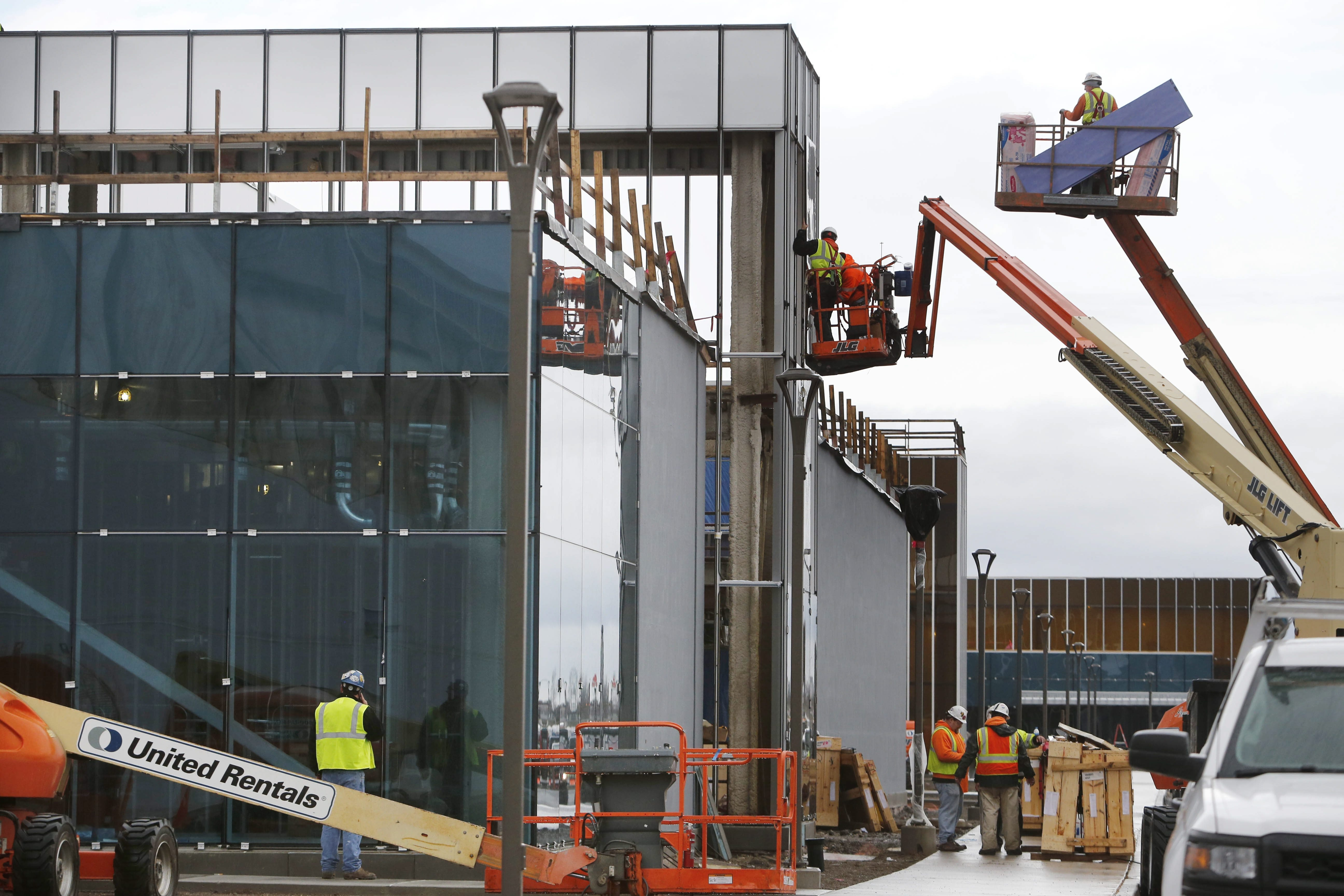 Workers in lifts outside a portion of the enormous Solar City facility under construction at RiverBend on Dec. 22. (Derek Gee/News file photo)